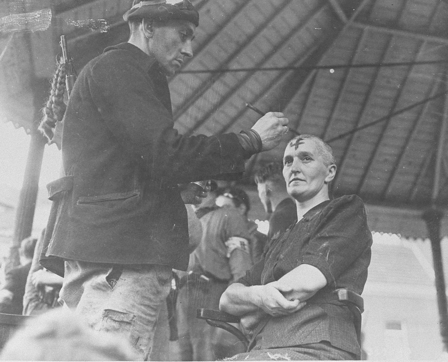 A member of the Belgian resistance paints a swastika on the forehead of a woman who collaborated with the Germans during the occupation of Belgium.  The resistance shaved her head and the heads of four other women in Lanaken as part of their public humilation.