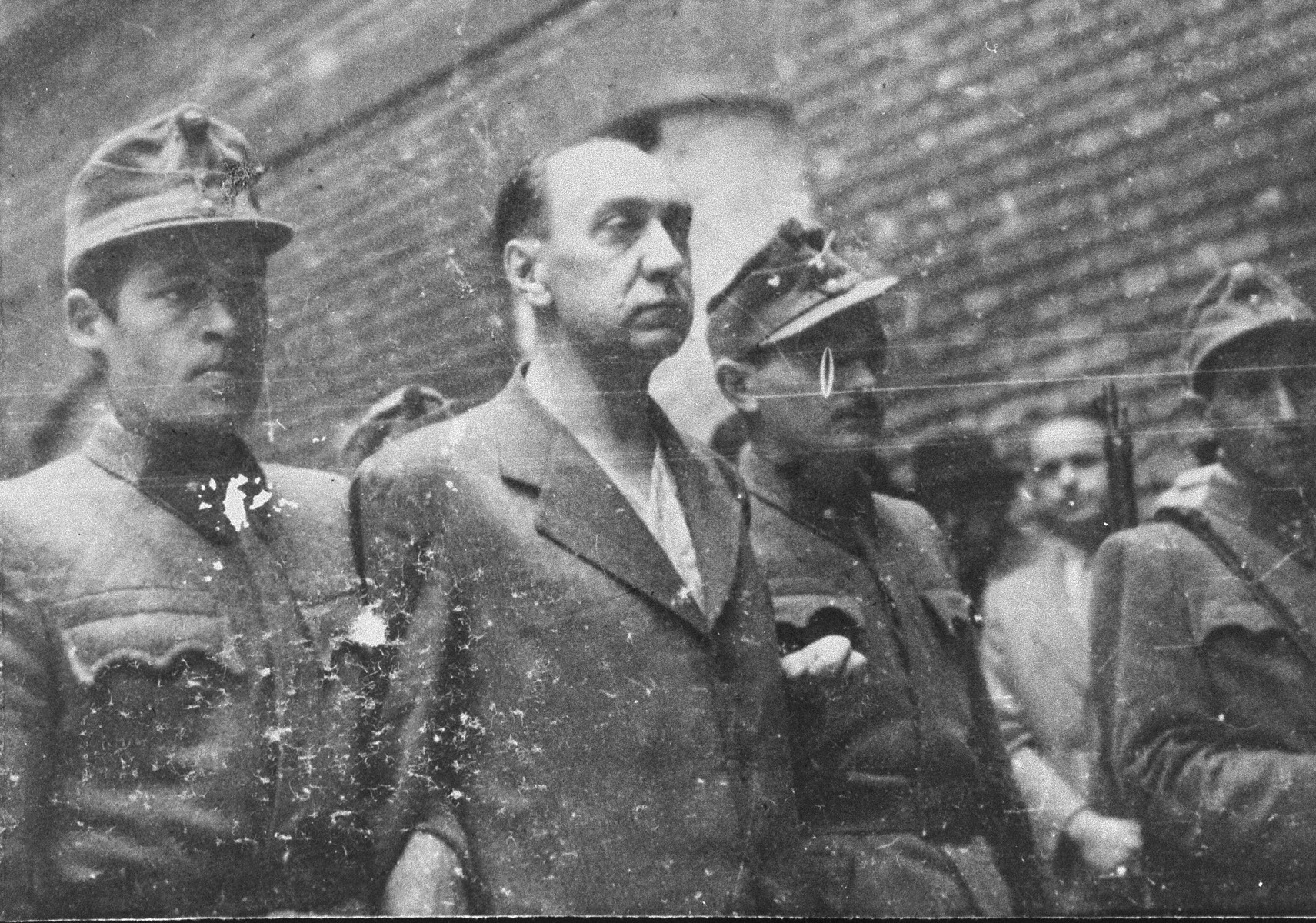 Hungarian soldiers lead former minister Lajos Remenyi-Schneller to execution in the courtyard of the Budapest Academy of Music.  Remenyi-Schneller was tried along with Dome Sztojay, Antal Kunder, Jeno Ratz, and Lajos Szasz by a People's Tribunal in the Budapest Academy of Music for his role in both the destruction of Hungarian Jewry and for sacrificing his country's interests by collaborating with the Third Reich.  The trial began on March 14, 1946 and ended only 8 days later on March 22, 1946 when all of the defendants were convicted, and subsequently executed.