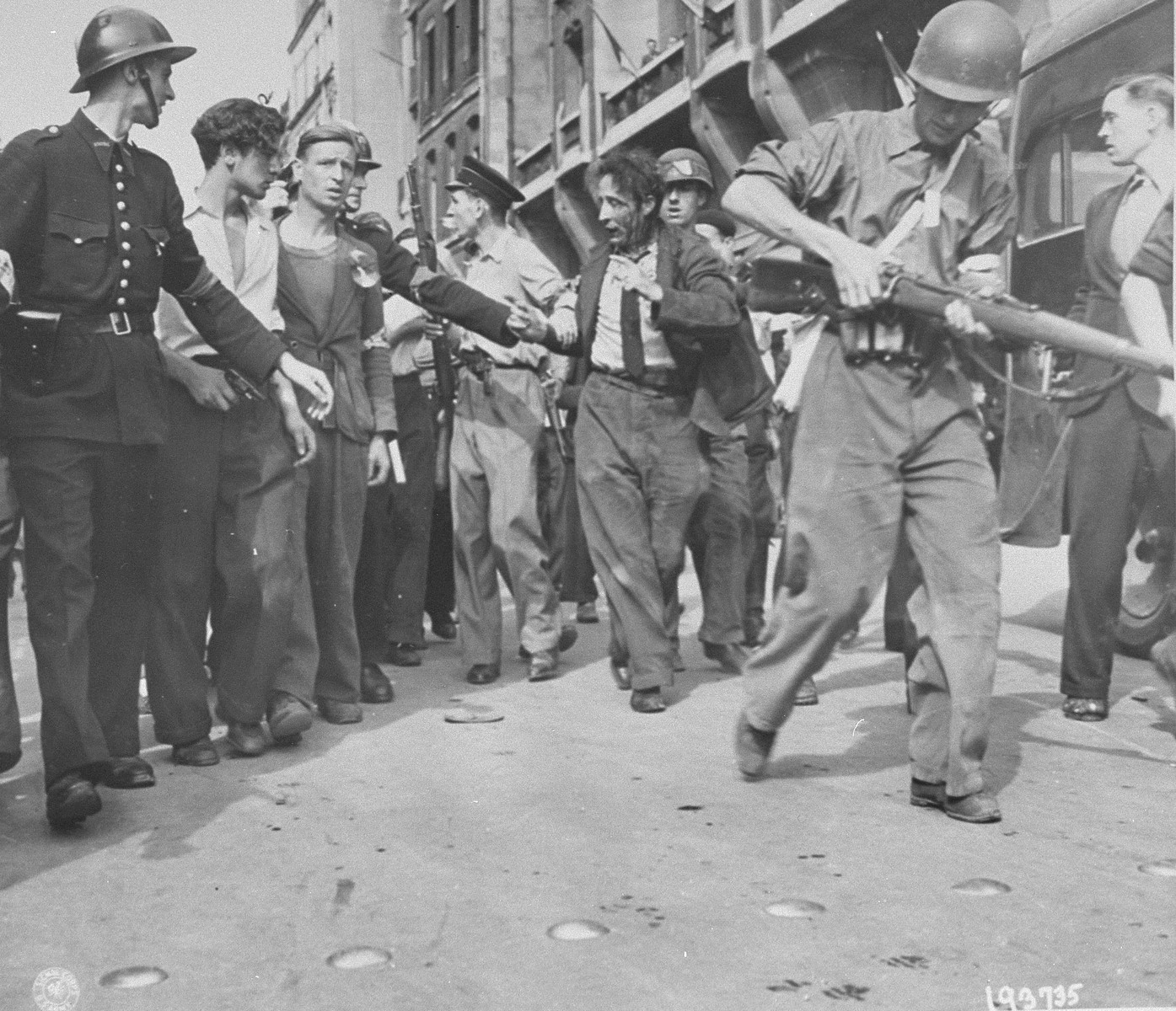 Members of the French resistance lead a wounded collaborator away from a crowd after he was beaten in the street on the day Paris was liberated.