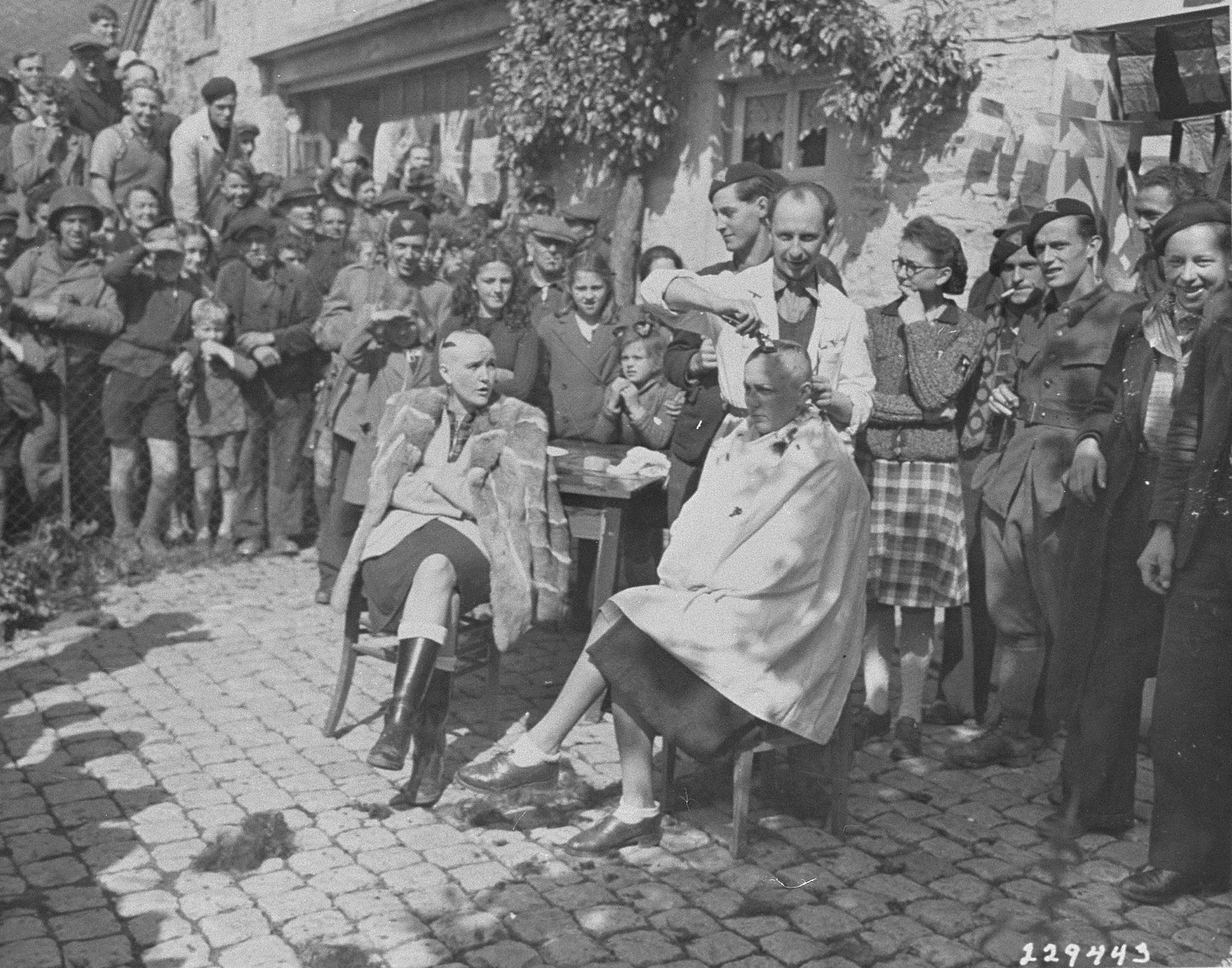 Belgian civilians and members of the resistance watch as a barber shaves the head of a woman who collaborated with the Nazis.  The woman at left has also had a swastika painted on her head.