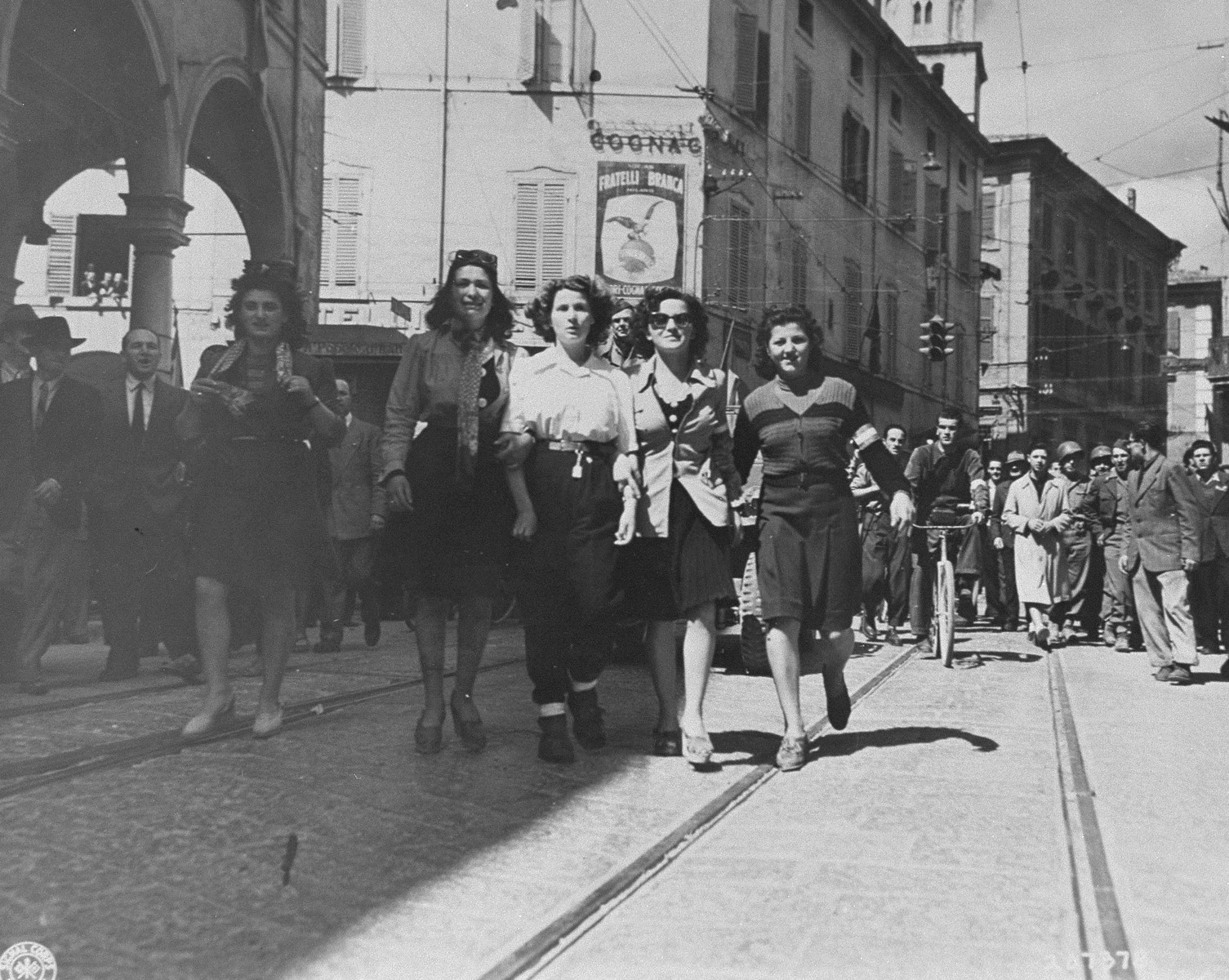 A woman accused of collaborating with the Germans is paraded through the streets of Modena by women members of the resistance.