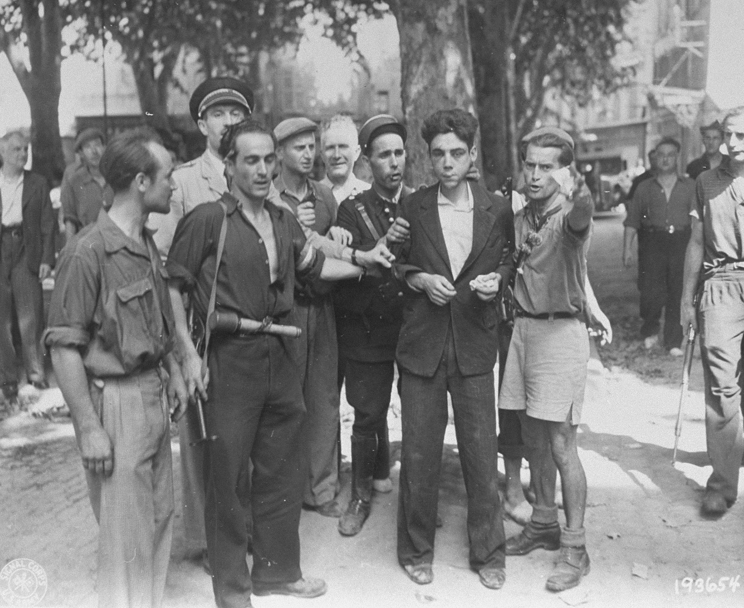 Members of the French resistance in Aix-en-Provence parade a beaten collaborator through the streets of the city.