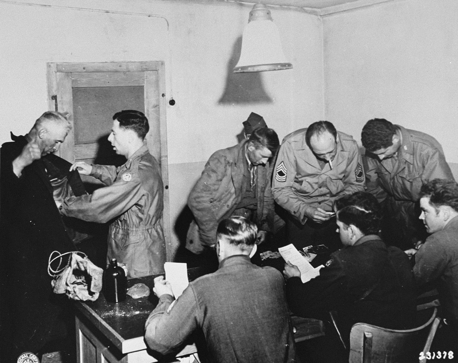 """U.S. troops search new German prisoners upon their arrival at the internment camp at Recklinghausen established by the U.S. Ninth Army.  When U.S. Ninth Army troops captured the concentration camp for Soviet civilians located near Recklinghausen, Germany, they converted it into a separation center for prisoners of war and war criminals.  After the first German prisoners arrived at the camp they were sent to the interrogation department, which was supervised by Captain Harold Puttfer and Lieutenant H. Goodman.  The camp had three sections called """"cages.""""  One of these was for women, another for persons incarcerated for minor offenses, and the third for hardened criminals.  All three sections were filled to capacity, totalling 20,000 prisoners."""