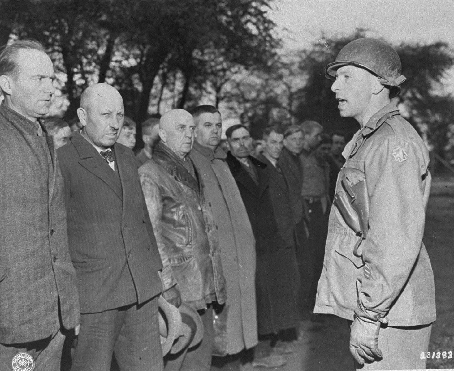"An American officer speaks to new German prisoners upon their arrival at the Recklinghausen internment camp, which was established by the U.S. Ninth Army.  When U.S. Ninth Army troops captured the concentration camp for Soviet civilians located near Recklinghausen, Germany, they converted it into a separation center for prisoners of war and war criminals.  After the first German prisoners arrived at the camp they were sent to the interrogation department, which was supervised by Captain Harold Puttfer and Lieutenant H. Goodman.  The camp had three sections called ""cages.""  One of these was for women, another for persons incarcerated for minor offenses, and the third for hardened criminals.  All three sections were filled to capacity, totalling 20,000 prisoners."
