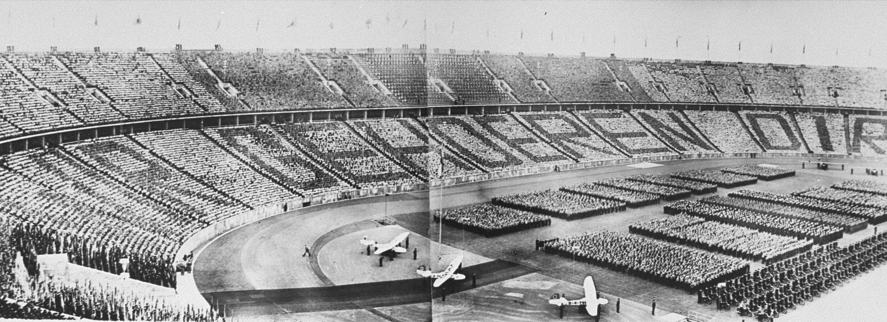 """Aerial view of the Olympic stadium in Berlin, site of the 11th Olympiad, during one of the main ceremonies.  Germans carrying flags, or wearing dark uniforms, spell out the phrase """"Wir gehoeren dir"""" [We belong to you]."""