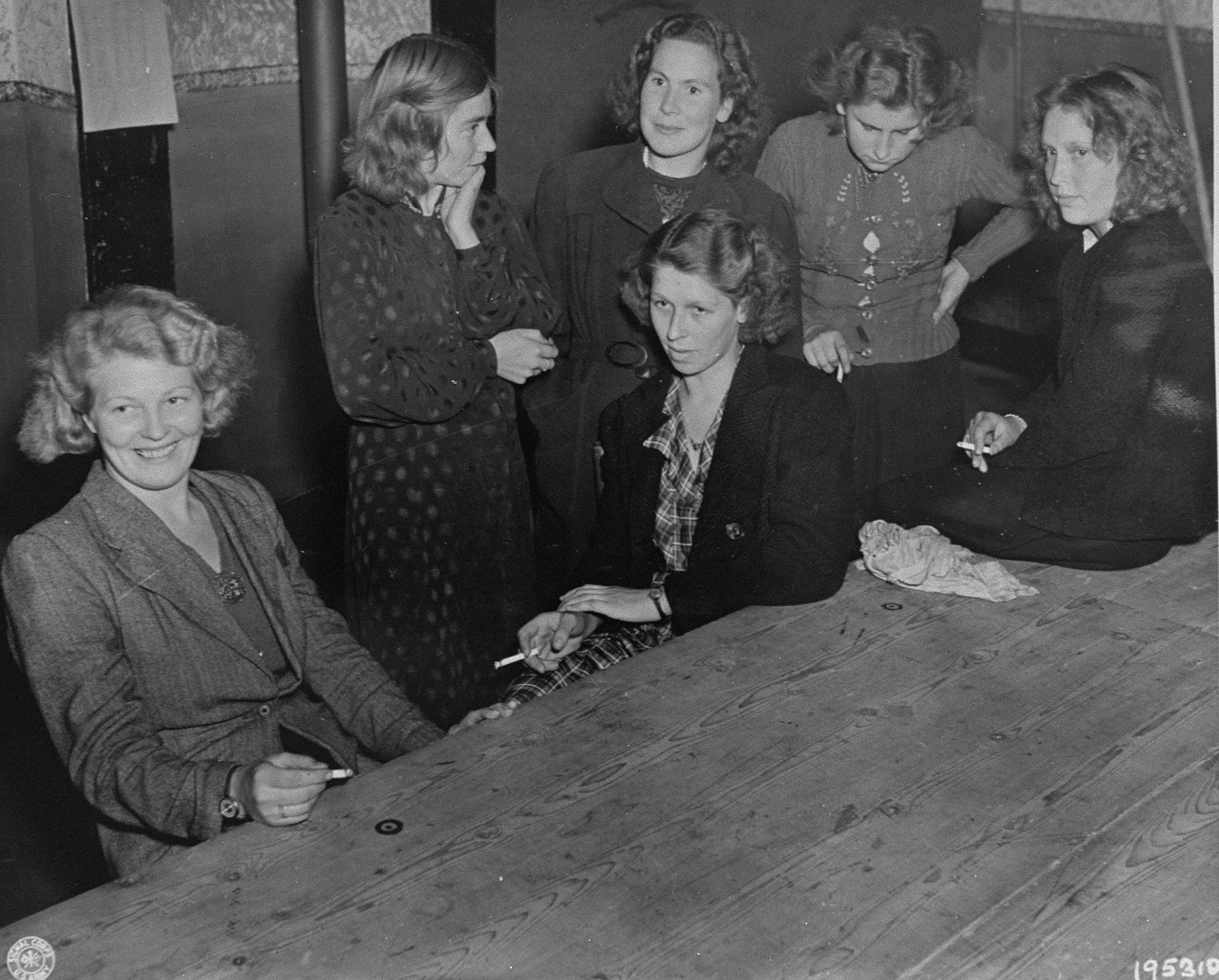 Women accused of collaborating with the Germans await their fate after being arrested by the Dutch resistance.  Their heads will be shaved and they will be marched through the streets of Grave.