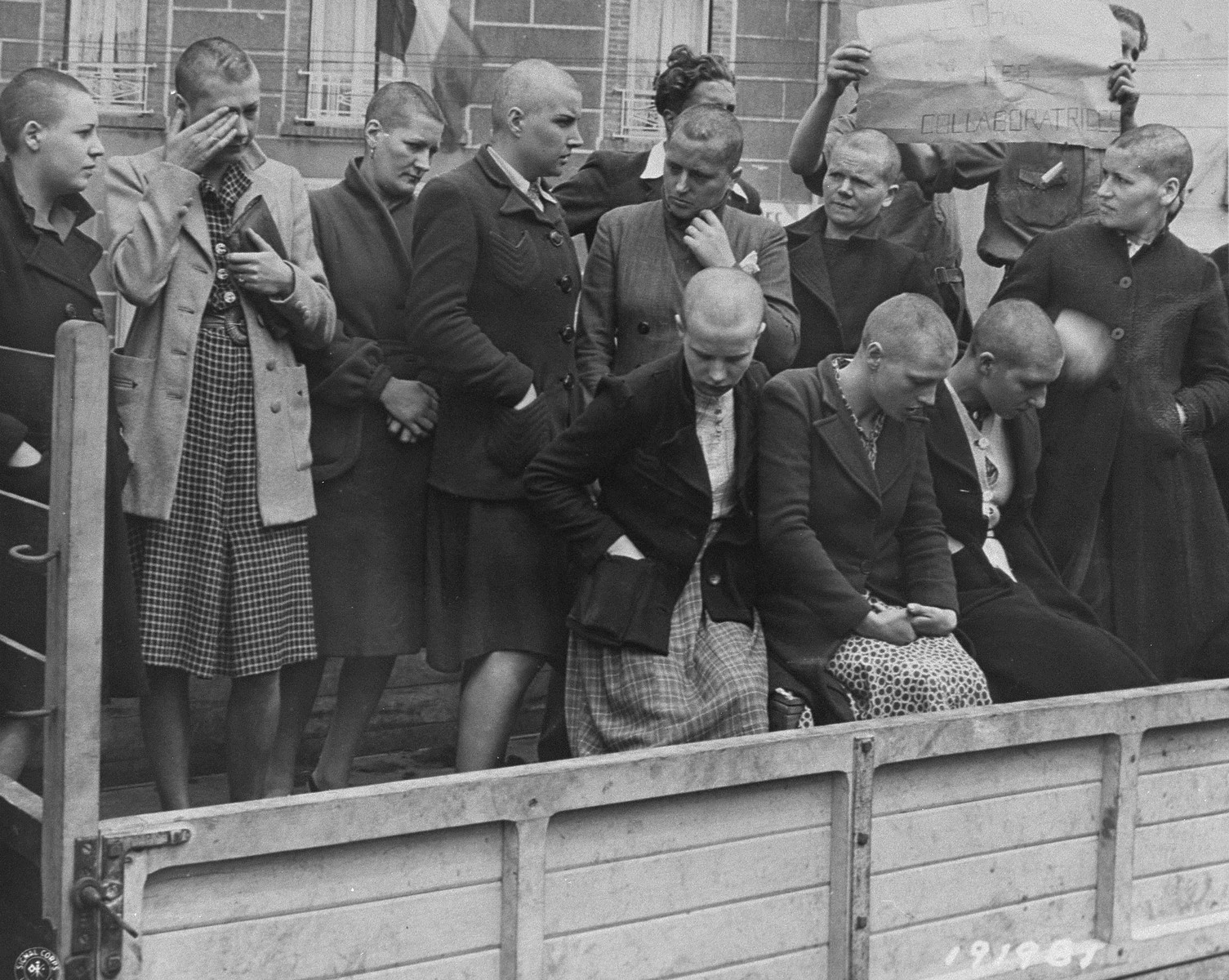Women who consorted with the Germans during the occupation are driven through the streets of Cherbourg by members of the French resistance.  Their head were shaven in order to humiliate them.