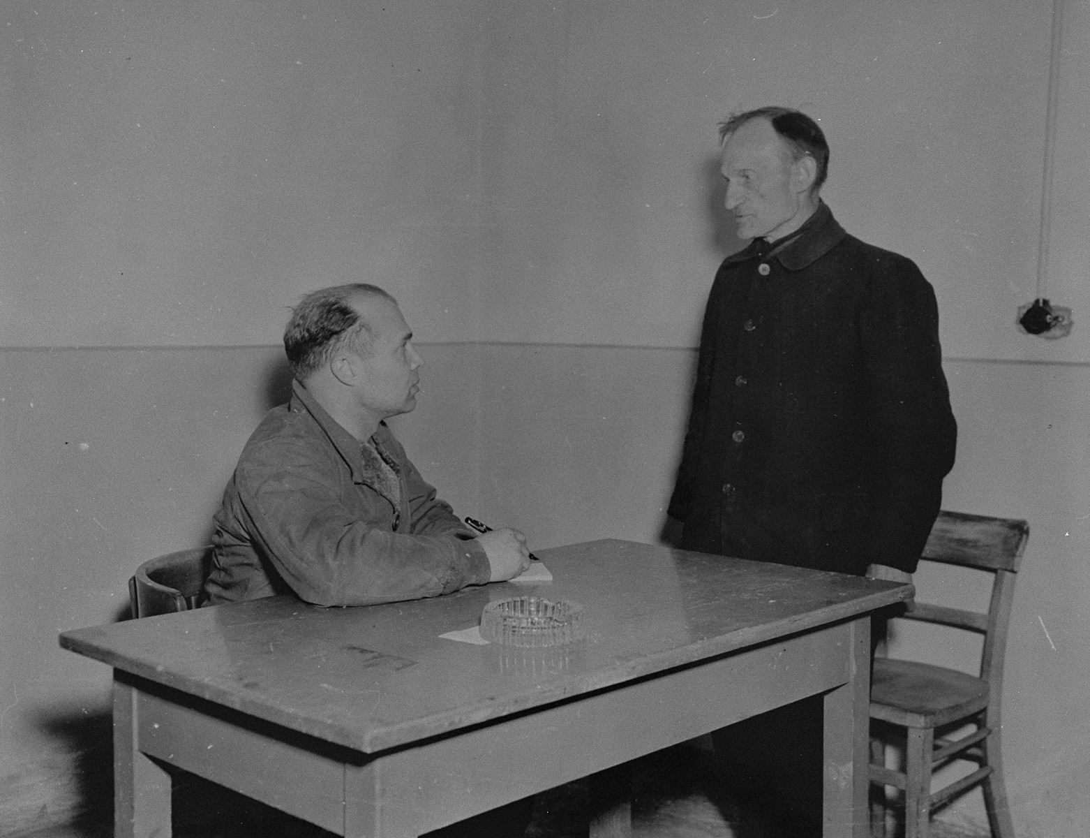 "An American investigator from the 79th Infantry Division, U.S. Ninth Army, questions Willi Fabian, a former railroad official and staff member in the Rothensee concentration camp.  Fabian was charged with mistreating laborers from Allied nations and was arrested on April 19, 1945 in Barleben, Germany.  When U.S. Ninth Army troops captured the concentration camp for Soviet civilians located near Recklinghausen, Germany, they converted it into a separation center for prisoners of war and war criminals.  After the first German prisoners arrived at the camp they were sent to the interrogation department, which was supervised by Captain Harold Puttfer and Lieutenant H. Goodman.  The camp had three sections called ""cages.""  One of these was for women, another for persons incarcerated for minor offenses, and the third for hardened criminals.  All three sections were filled to capacity, totalling 20,000 prisoners."