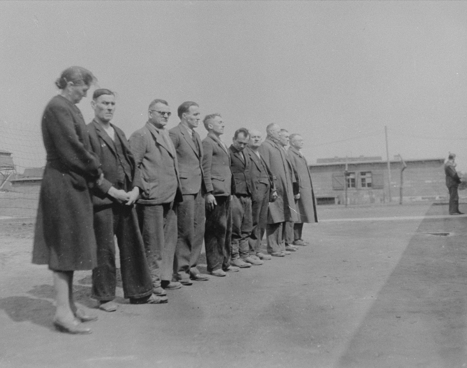 "Ten German prisoners held in the Recklinghausen internment camp wait to be questioned by American investigators from the U.S. Ninth Army for their roles in the alleged murder of American pilots and the mistreatment of slave labores and prisoners during the war.  When U.S. Ninth Army troops captured the concentration camp for Soviet civilians located near Recklinghausen, Germany, they converted it into a separation center for prisoners of war and war criminals.  After the first German prisoners arrived at the camp they were sent to the interrogation department, which was supervised by Captain Harold Puttfer and Lieutenant H. Goodman.  The camp had three sections called ""cages.""  One of these was for women, another for persons incarcerated for minor offenses, and the third for hardened criminals.  All three sections were filled to capacity, totalling 20,000 prisoners."