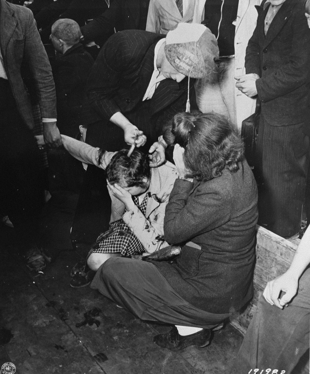 Members of the French resistance in Cherbourg shear the hair of women who collaborated with the Germans during the occupation.  The women were then paraded though the streets of the city.
