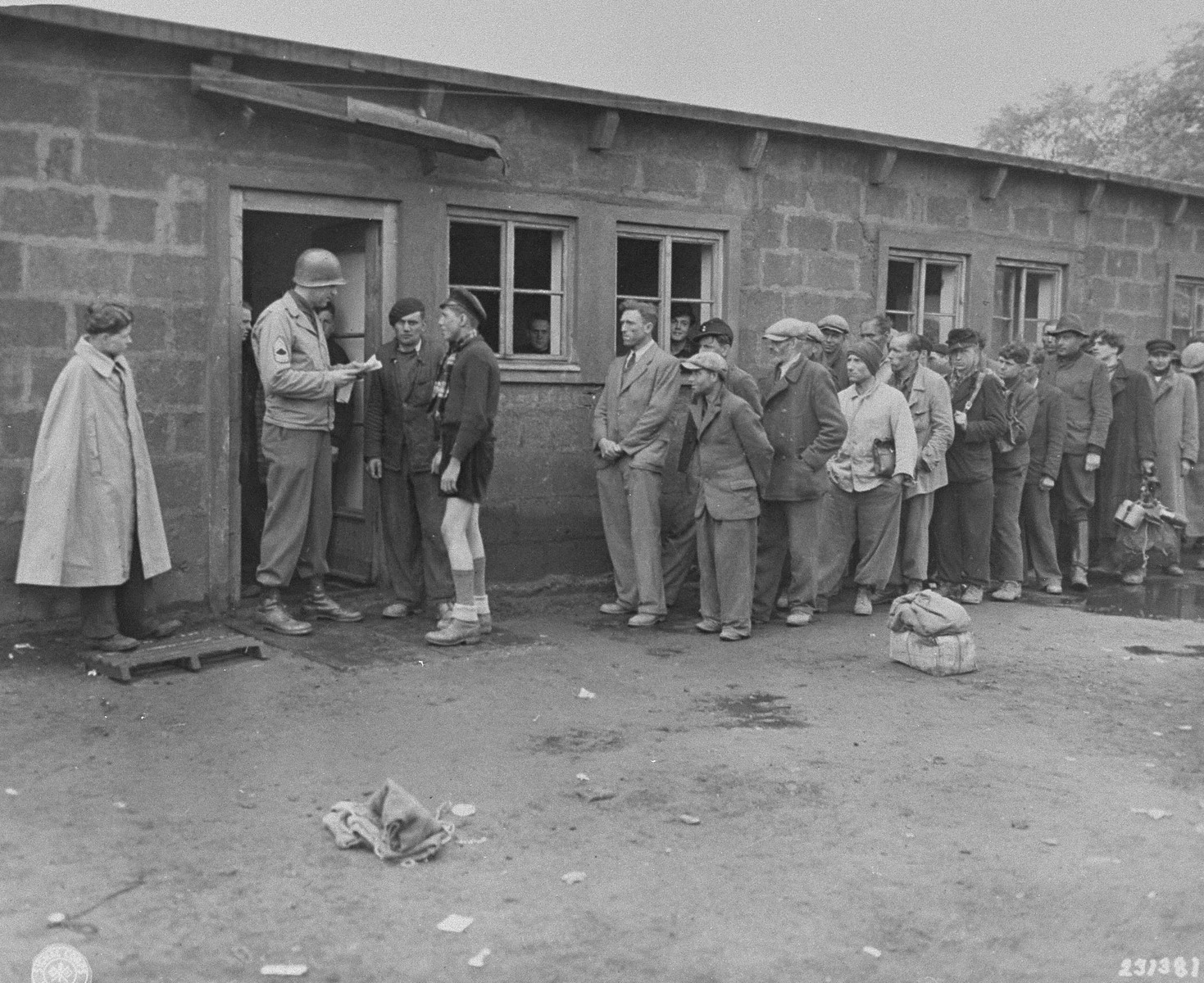 "A U.S. Army sergeant checks the papers of new German prisoners lined up outside of the processing center of the Recklinghausen internment camp.  When U.S. Ninth Army troops captured the concentration camp for Soviet civilians located near Recklinghausen, Germany, they converted it into a separation center for prisoners of war and war criminals.  After the first German prisoners arrived at the camp they were sent to the interrogation department, which was supervised by Captain Harold Puttfer and Lieutenant H. Goodman.  The camp had three sections called ""cages.""  One of these was for women, another for persons incarcerated for minor offenses, and the third for hardened criminals.  All three sections were filled to capacity, totalling 20,000 prisoners."