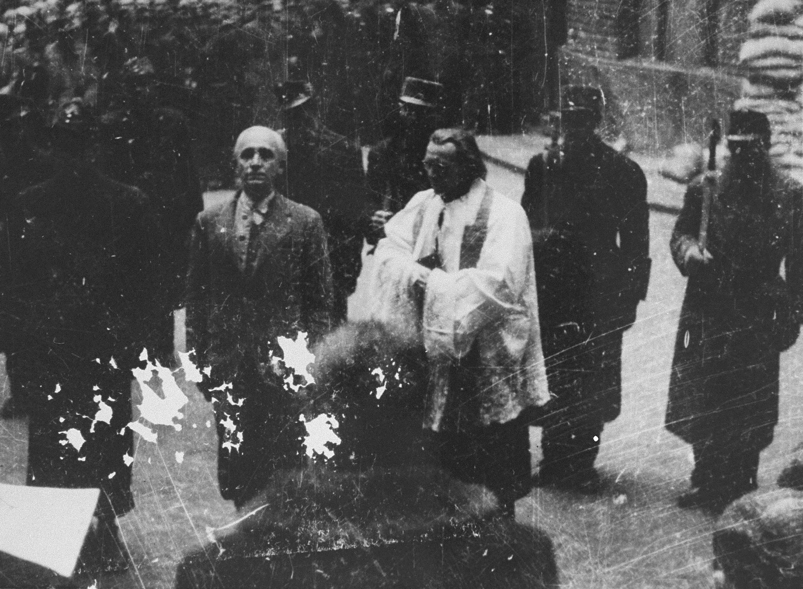 A Hungarian official reads the death sentence of former Prime Minister Dr.  Laszlo V.  Bardossy prior to his execution in the courtyard of the Academy of Music in Budapest.  The trial of Laszlo V. Bardossy was the first postwar trial of a suspected Hungarian war criminal to be carried out by the People's Tribunal in the Academy of Music in Budapest.  Bardossy was charged as former prime minister with illegally involving Hungary in war against the Soviet Union and with responsibility for allowing the massacre of Jews at Kamenets-Podolsk in July 1941.  Bardossy's trial was convened on October 29, 1945 and he was convicted on November 3, 1945.  His execution was carried out on January 10, 1946.