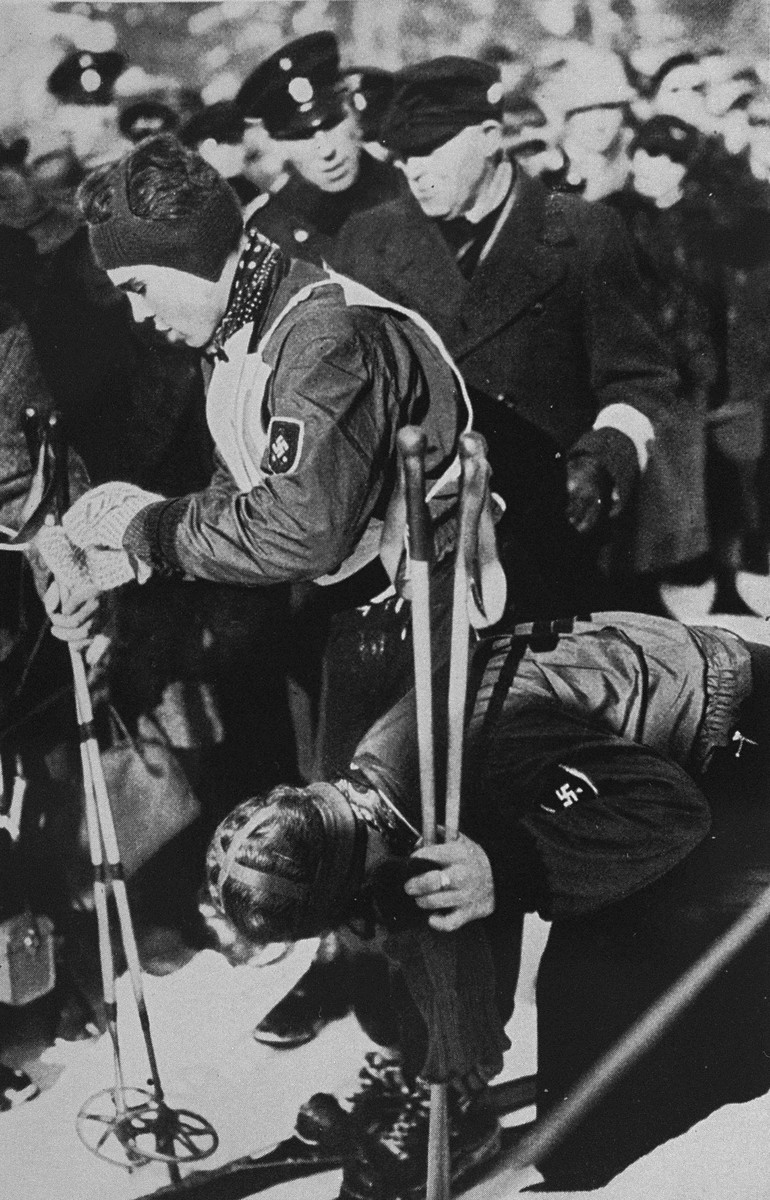 German Olympic skier Christl Cranz helps to unbuckle her brother's skis after a run.