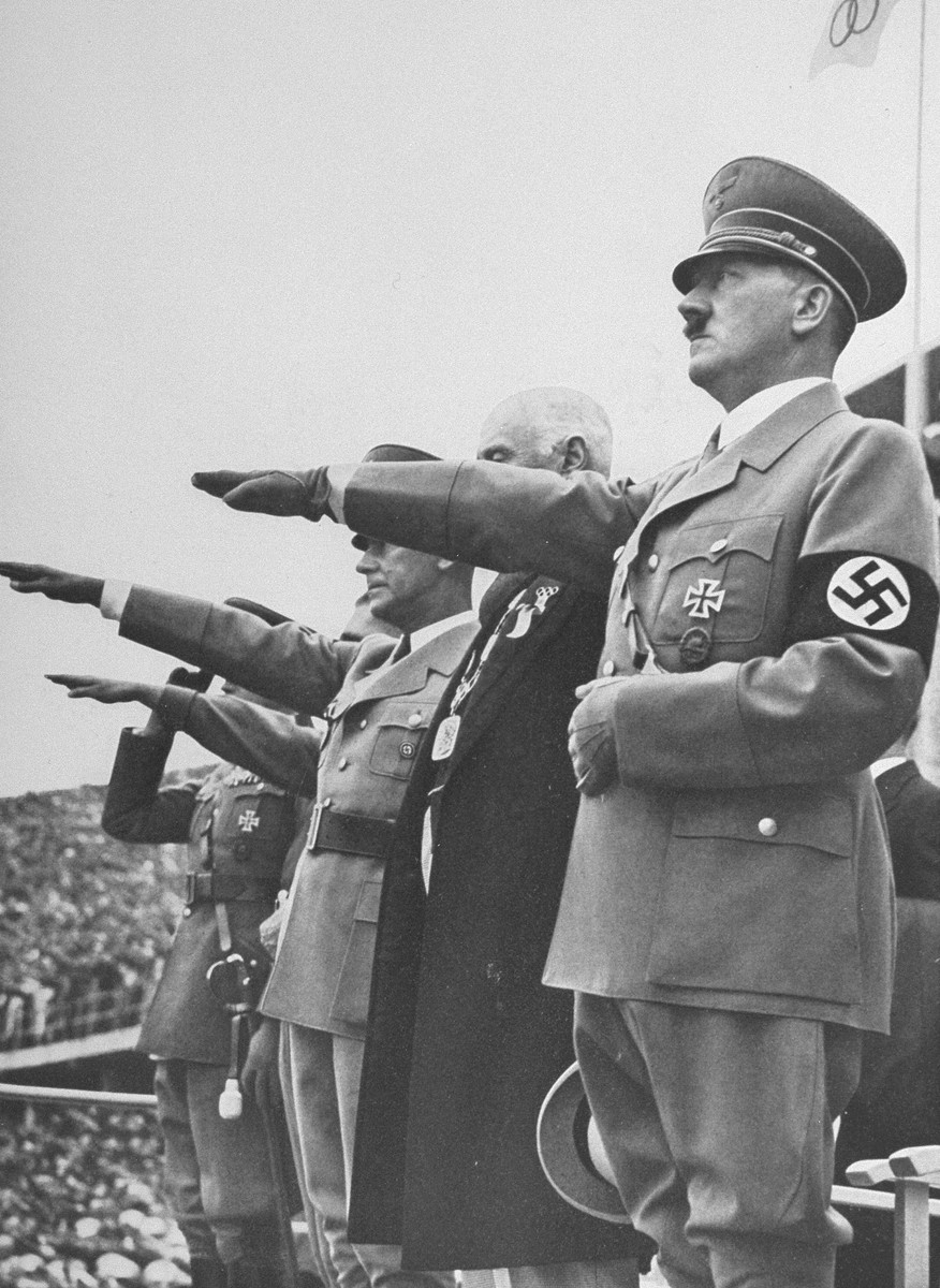 Adolf Hitler saluting the Olympic flag at the opening of the 1936 Olympic Games.  Pictured to his left are Italian Crown Prince Umberto to his left and former president of the German Olympic Committee, Dr. Theo Lewald, Rudolf Hess (partially obscured) and Werner von Blomberg, Minister of Defence