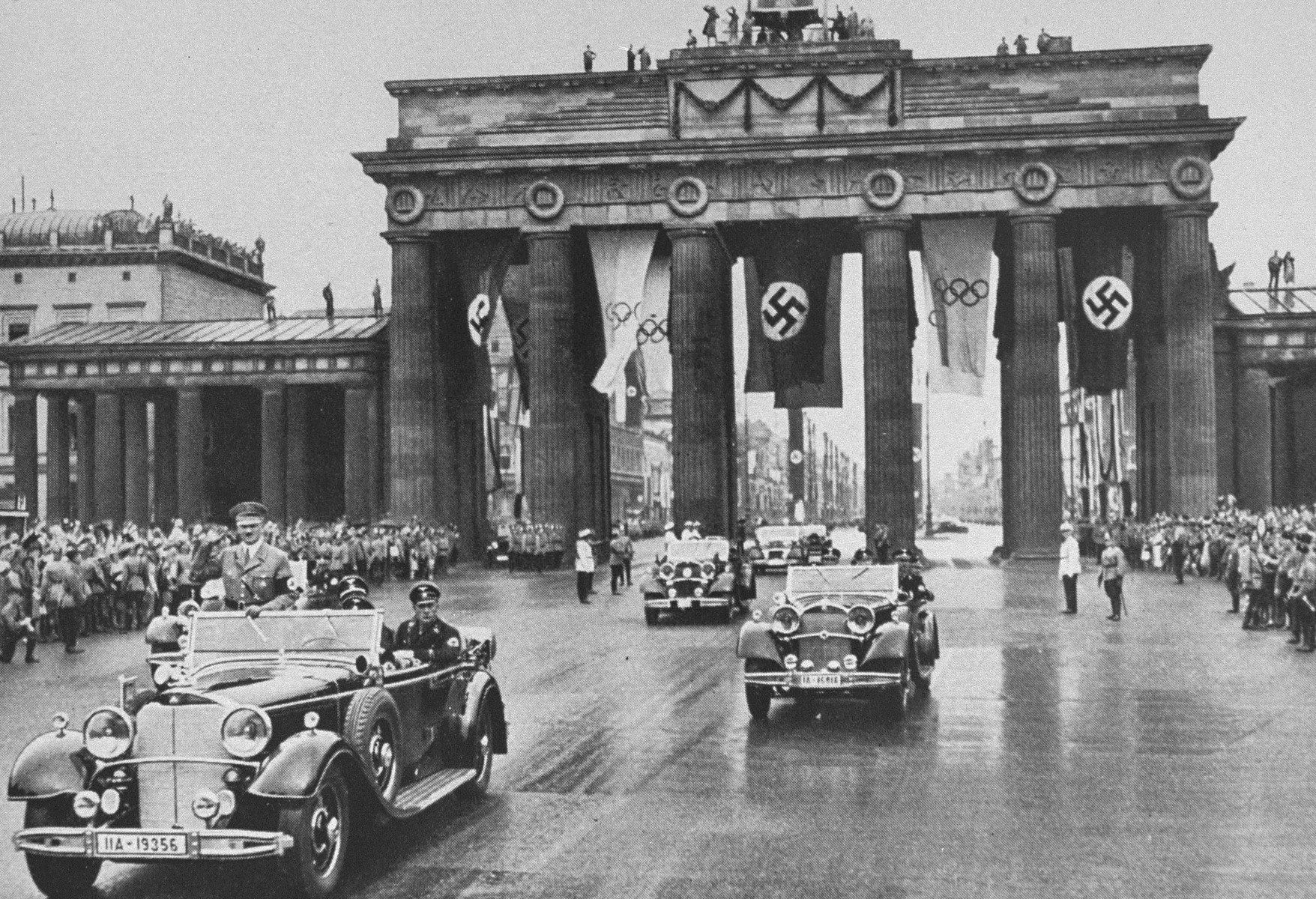 Adolf Hitler rides in a motorcade through the Brandenburg Gate to the opening ceremonies of the 11th Olympiad in Berlin.