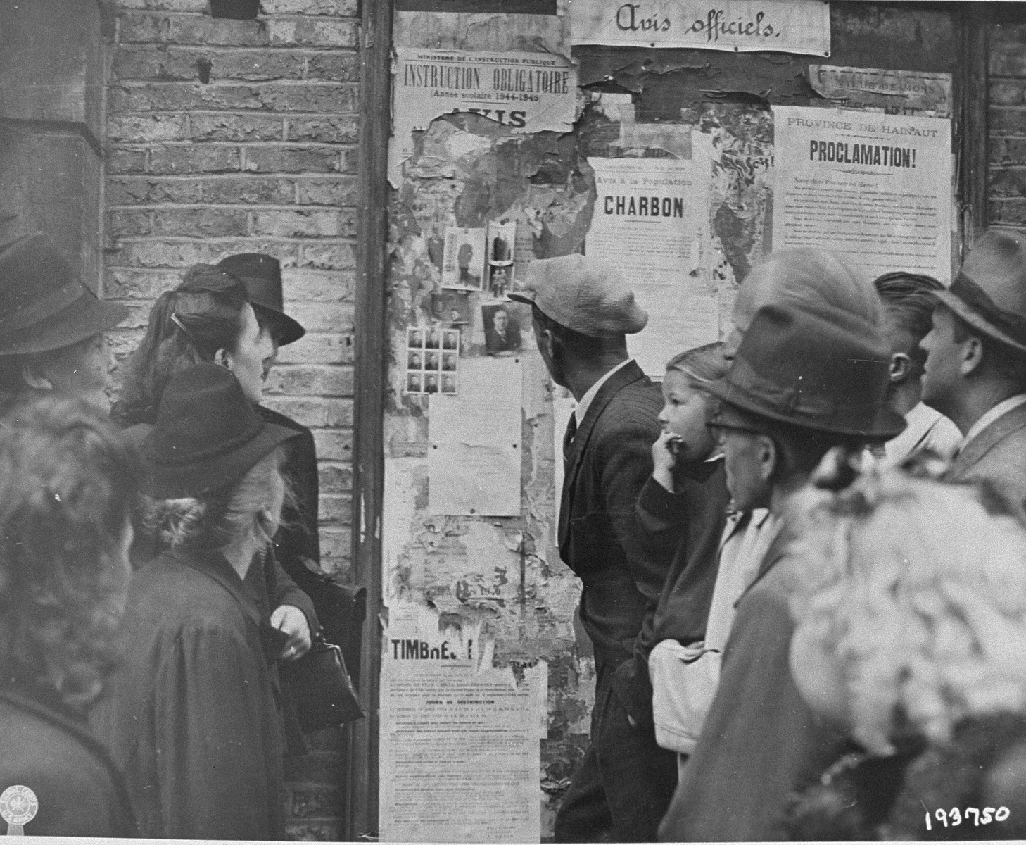 Some of the Belgian inhabitants of Mons look at the photos of collaborators posted on a public bulletin board.