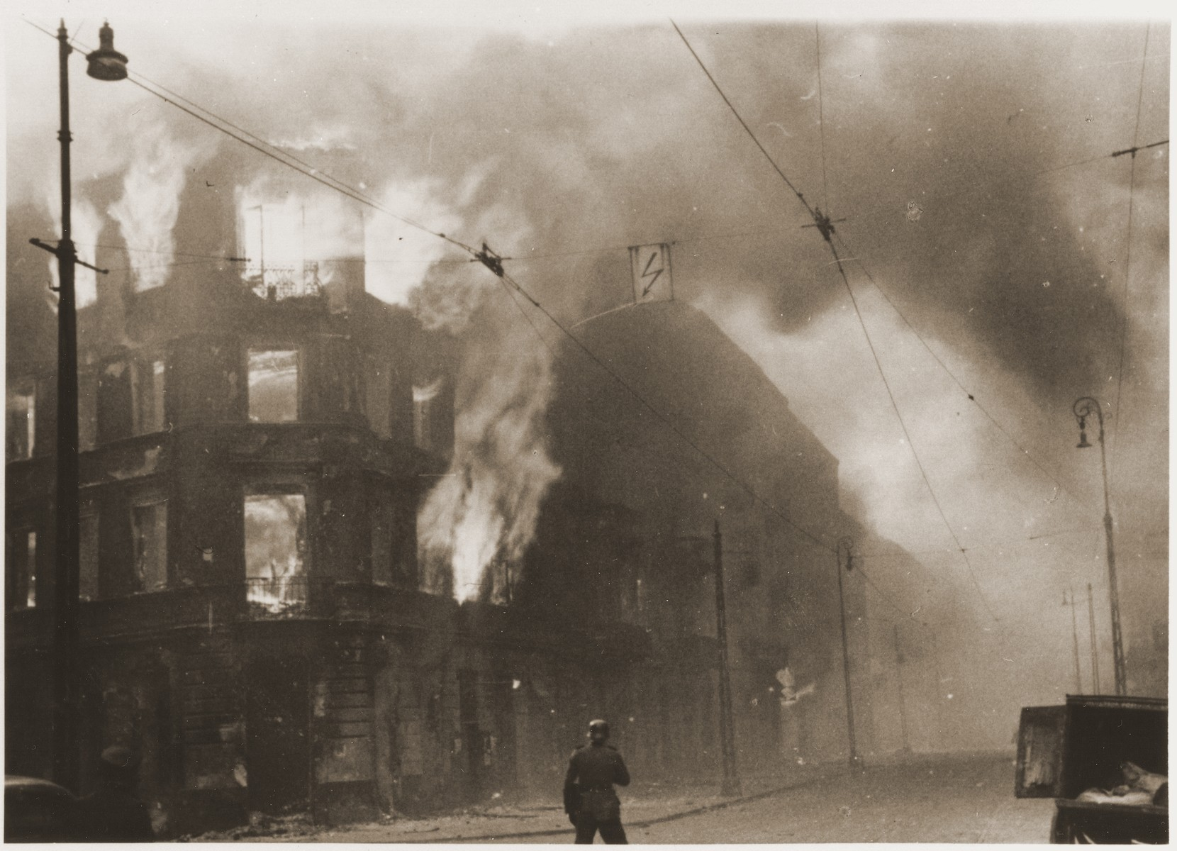 "A housing block burns during the suppression of the Warsaw ghetto uprising.    The original caption (translated from German) reads: ""Destruction of a housing block."""