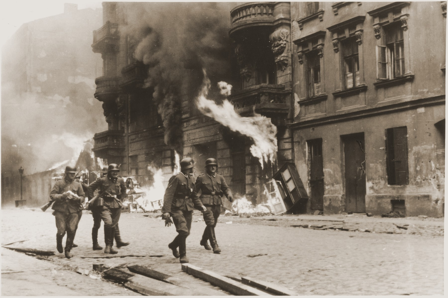 """SS troops walk past a block of burning housing during the suppression of the Warsaw ghetto uprising.  The original German caption reads: """"An assault squad."""""""