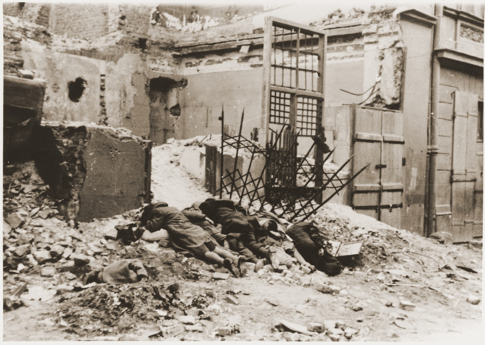 "The bodies of Jewish resisters lie in front of the ruins of a building where they were shot by the SS during the suppression of the Warsaw ghetto uprising.  The original German caption reads: ""Bandits killed in battle."""