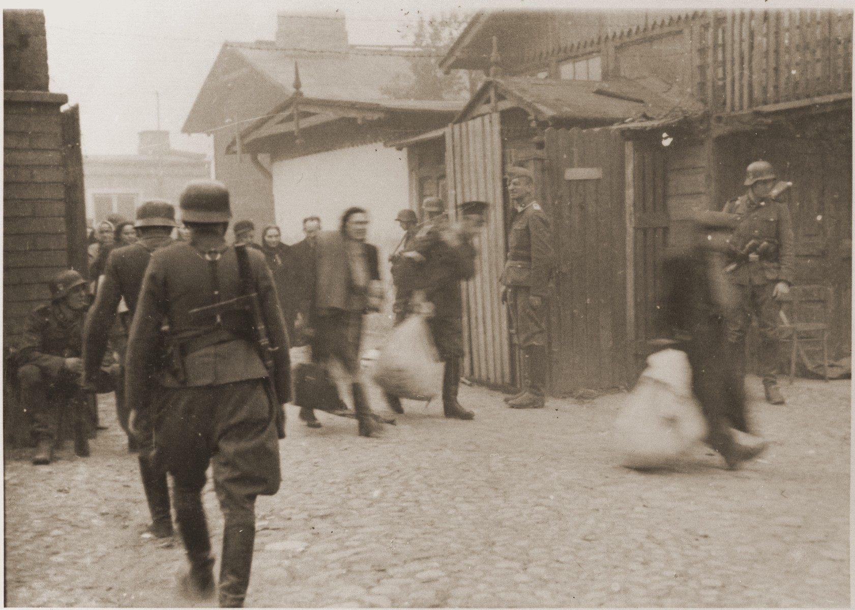 "Jewish laborers are forced by SS troops to evacuate a Warsaw ghetto factory during the uprising.    The original German caption reads: ""Vacating the factories!"""
