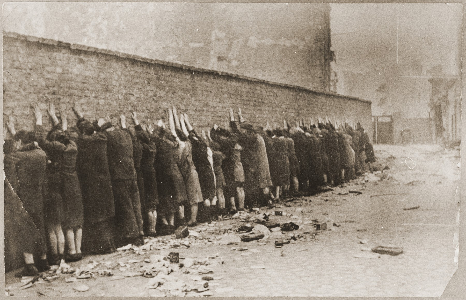 "Jews captured by the SS during the suppression of the Warsaw ghetto uprising are lined up against a wall prior to being searched for weapons.  The original German caption reads: ""Before the search.""   Original caption from donated photograph reads:  ""The following pictures are copies of the book conaning the report of the German commander who was responsible for cleaning out that ghetto in Warsaw, Poland.  This report, in the form of a leather bound book, was presented as evidence by the U.S. prosecution, Maj. Frank Walsh, at the international tribunal trials at Nurnberg, Germany."""