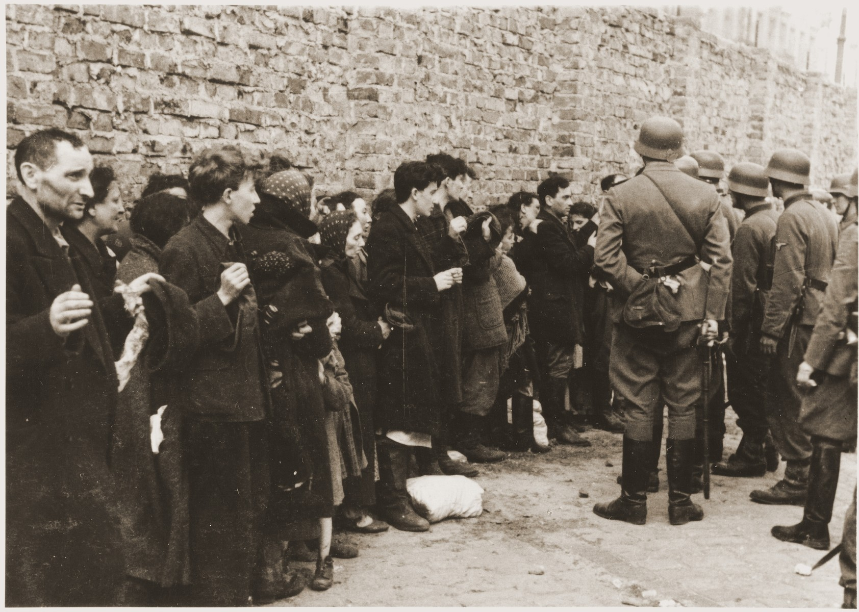 "Jews captured by the SS during the Warsaw ghetto uprising are interrogated beside the ghetto wall before being sent to the Umschlagplatz.  The original German caption reads: ""Search and Interrogation."""