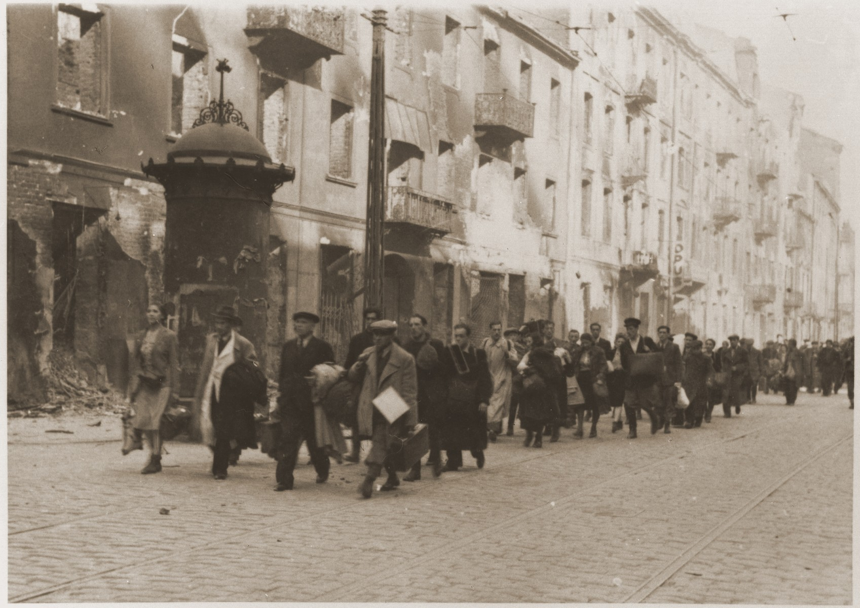 "Jews captured during the suppression of the Warsaw ghetto uprising are marched off to the Umschlagplatz for deportation.  The original German caption reads: ""March to the rail station."""