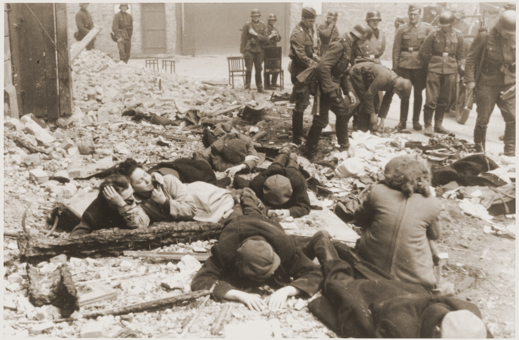 """SS troops search through scattered personal belongings as a small number of Jewish resistance fighters lie on the rubble nearby.  The original German caption reads: """"Just pulled from a bunker."""""""
