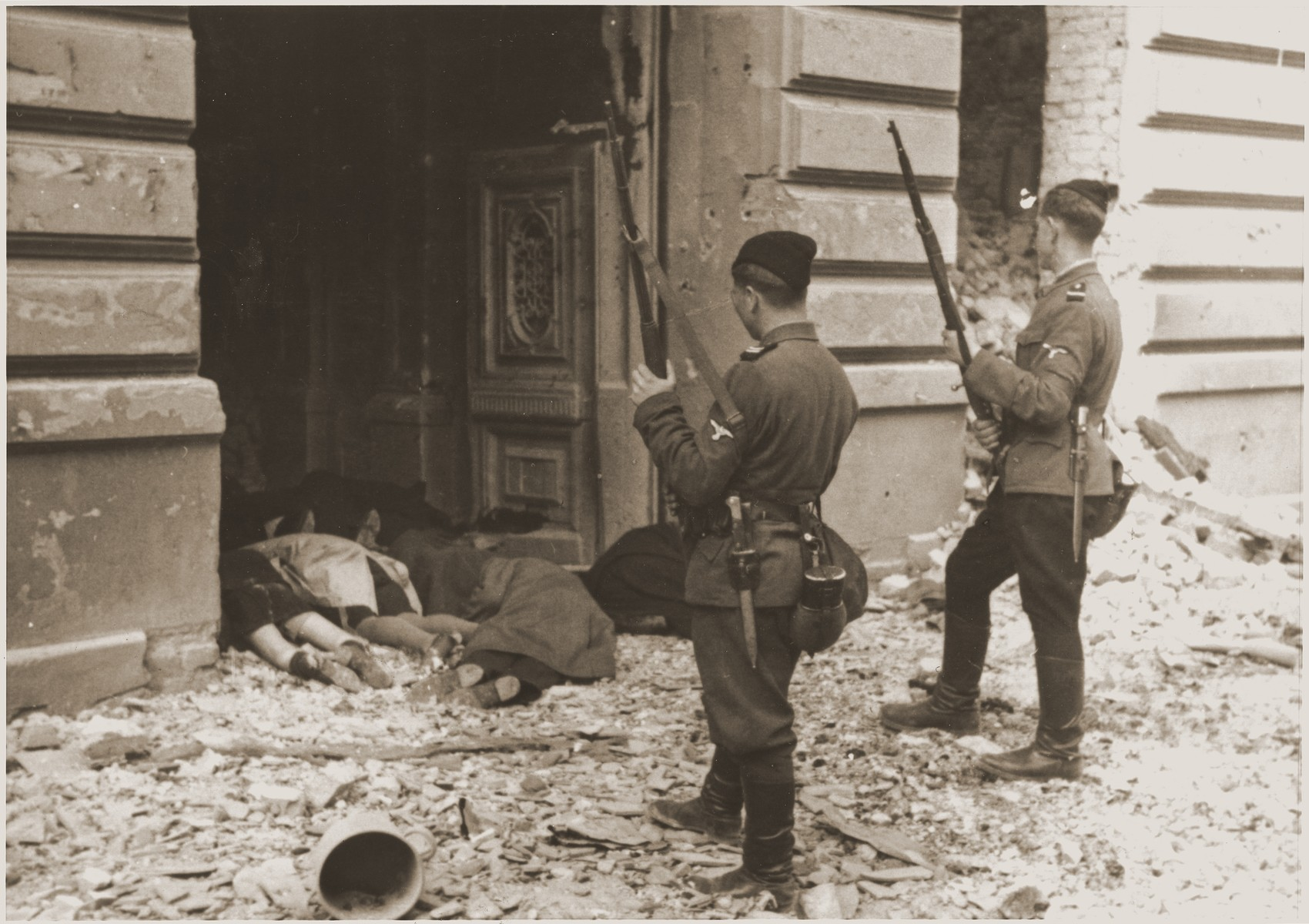 """Askari or Trawniki guards peer into a doorway past the bodies of Jews killed during the suppression of the Warsaw ghetto uprising.    The original German caption reads: """"Askaris used during the operation."""""""