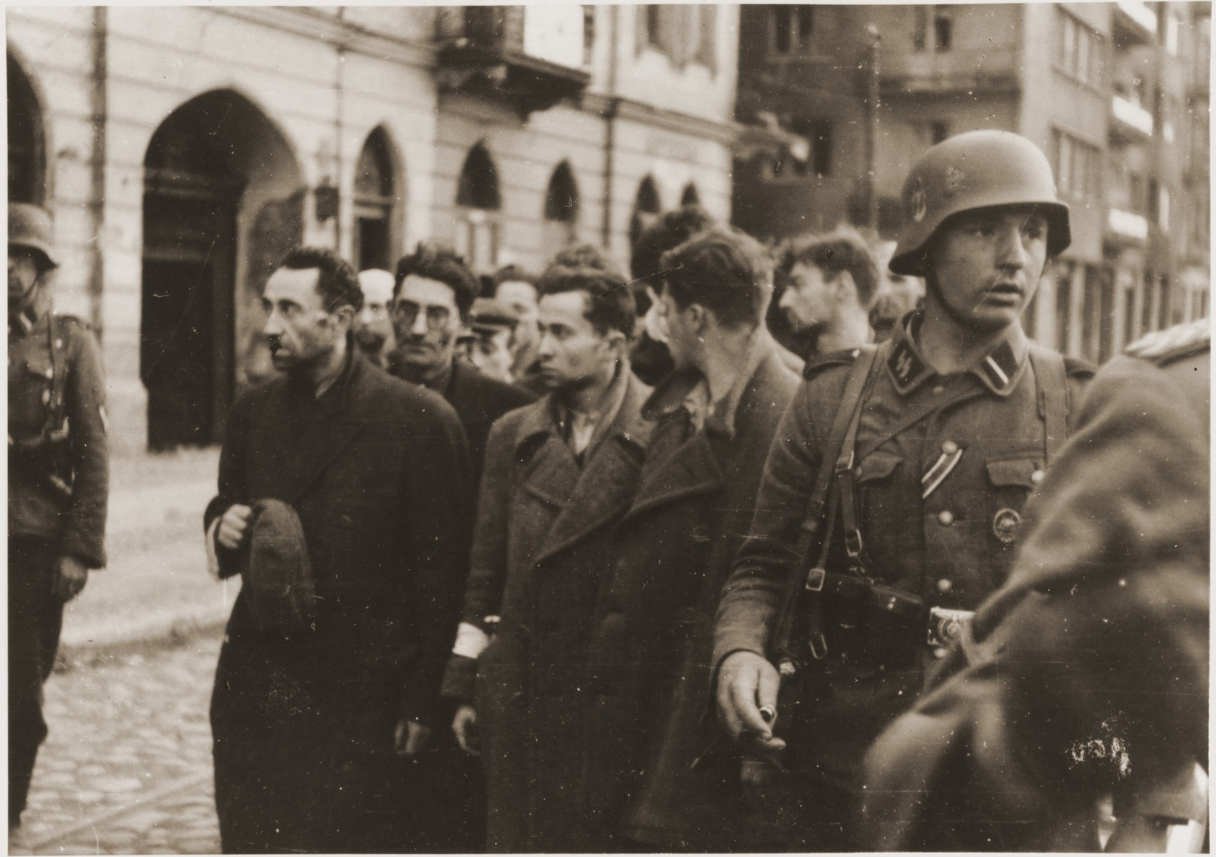 "SS troops guard members of the Jewish resistance captured during the suppression of the Warsaw ghetto uprising.  The original German caption reads: ""Bandits!"""