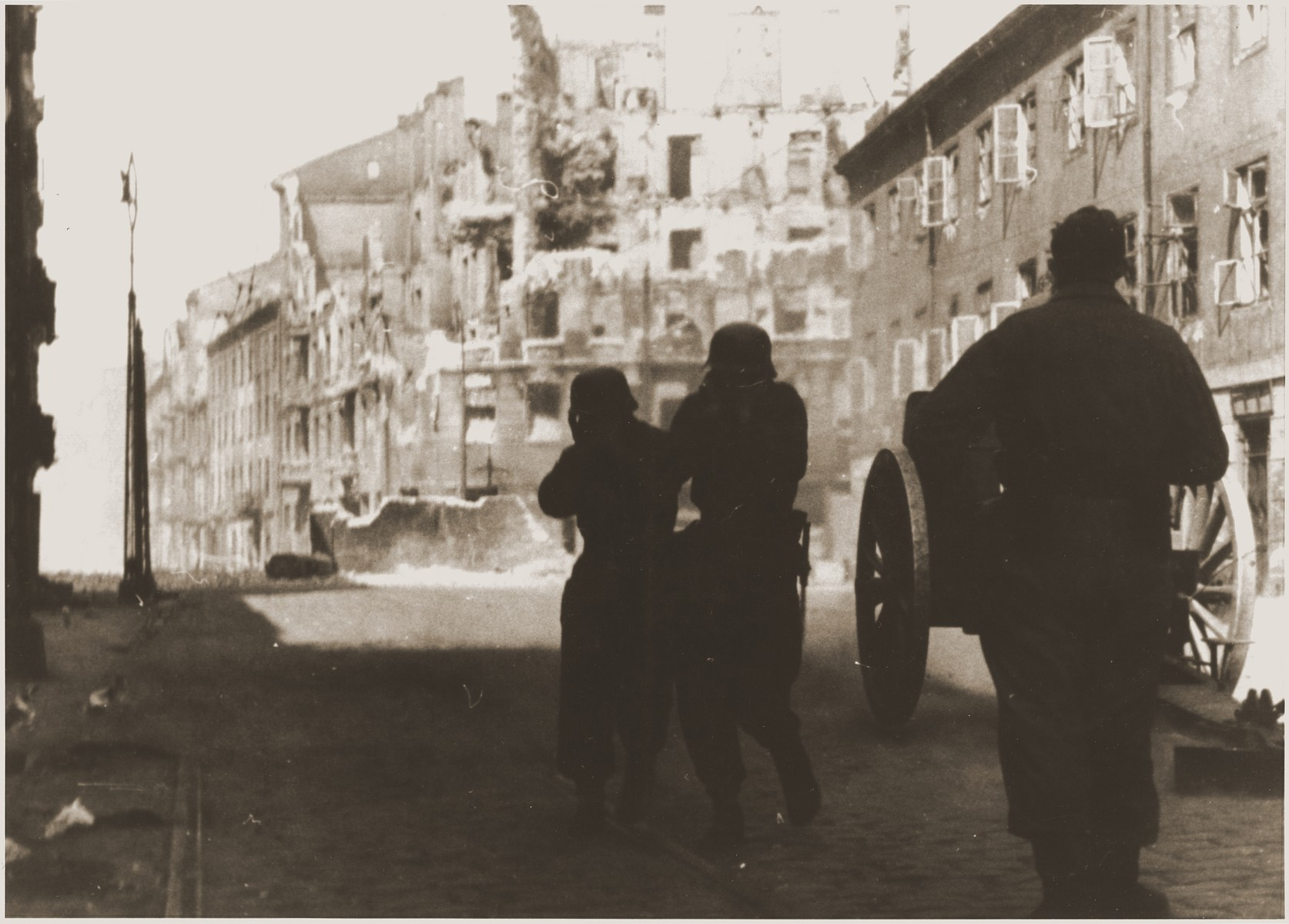 "A German gun crew shells a housing block during the suppression of the Warsaw ghetto uprising.  The original German caption reads: ""Destruction of a housing block."""