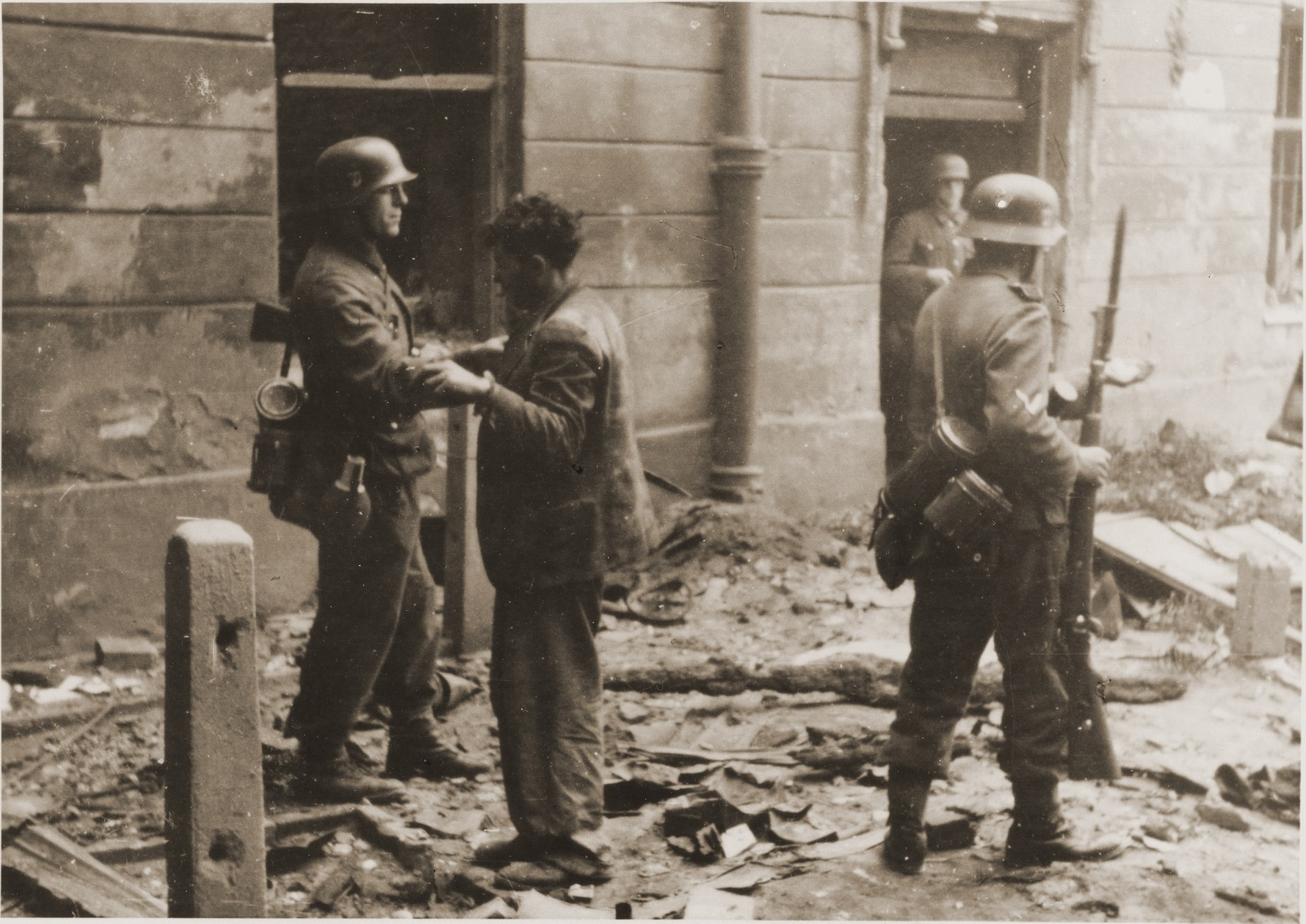 "An SS soldier searches a captured Jewish resistance fighter during the suppression of the Warsaw ghetto uprising.  The original German caption reads: ""Pulled from a bunker."""