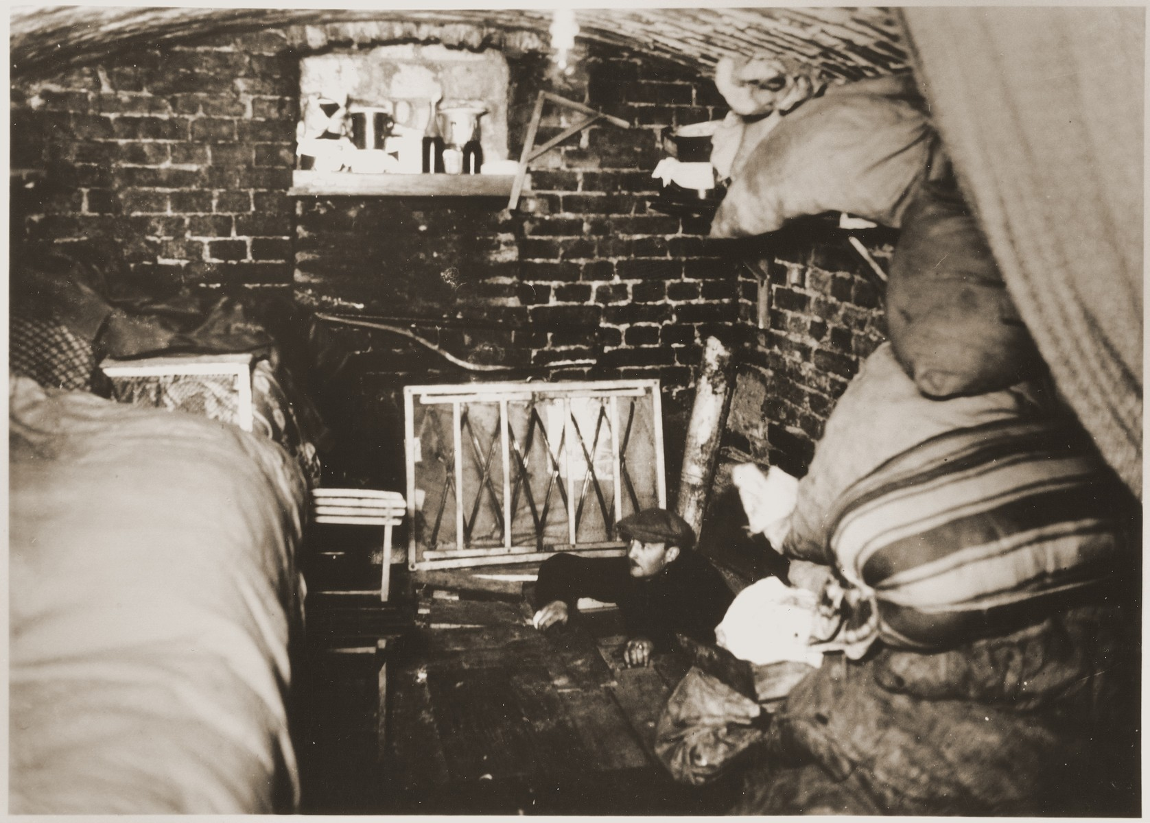 A Jewish man emerges from his hiding place below the floor of a bunker prepared for the Warsaw ghetto uprising.