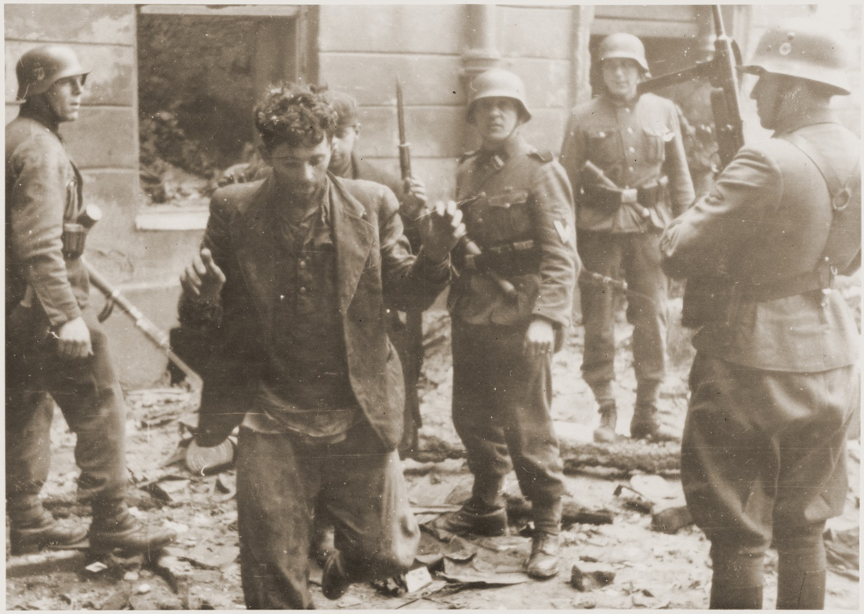 "SS assault troops capture two Jewish resistance fighters pulled from a bunker during the suppression of the Warsaw ghetto uprising.    The original caption (translated from German reads alternately: ""Pulled from a bunker"" or ""Bandits."""