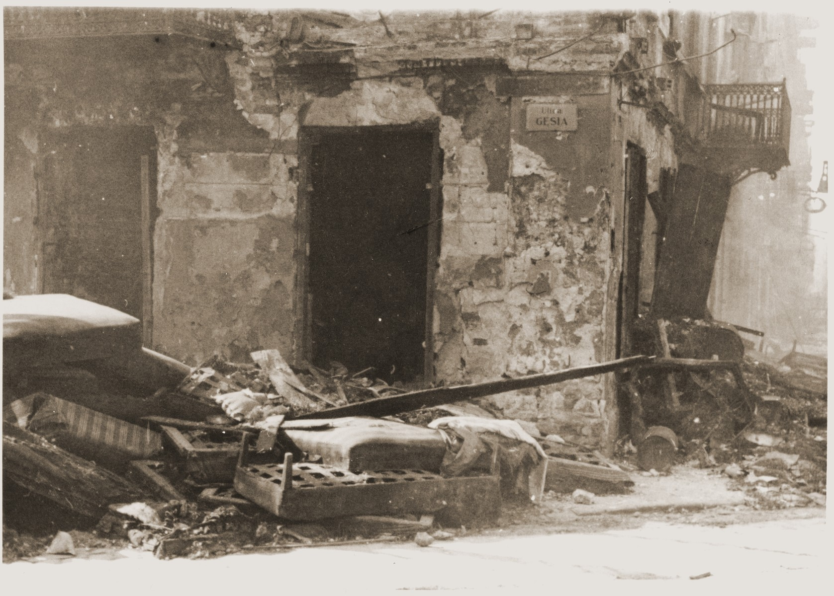 "Mattresses and furniture lie piled next to an apartment building on Gesia street to provide a place for the inhabitants to jump during the suppression of the Warsaw ghetto uprising.  The original German caption reads: ""A place that had been readied for jumping and escape."""