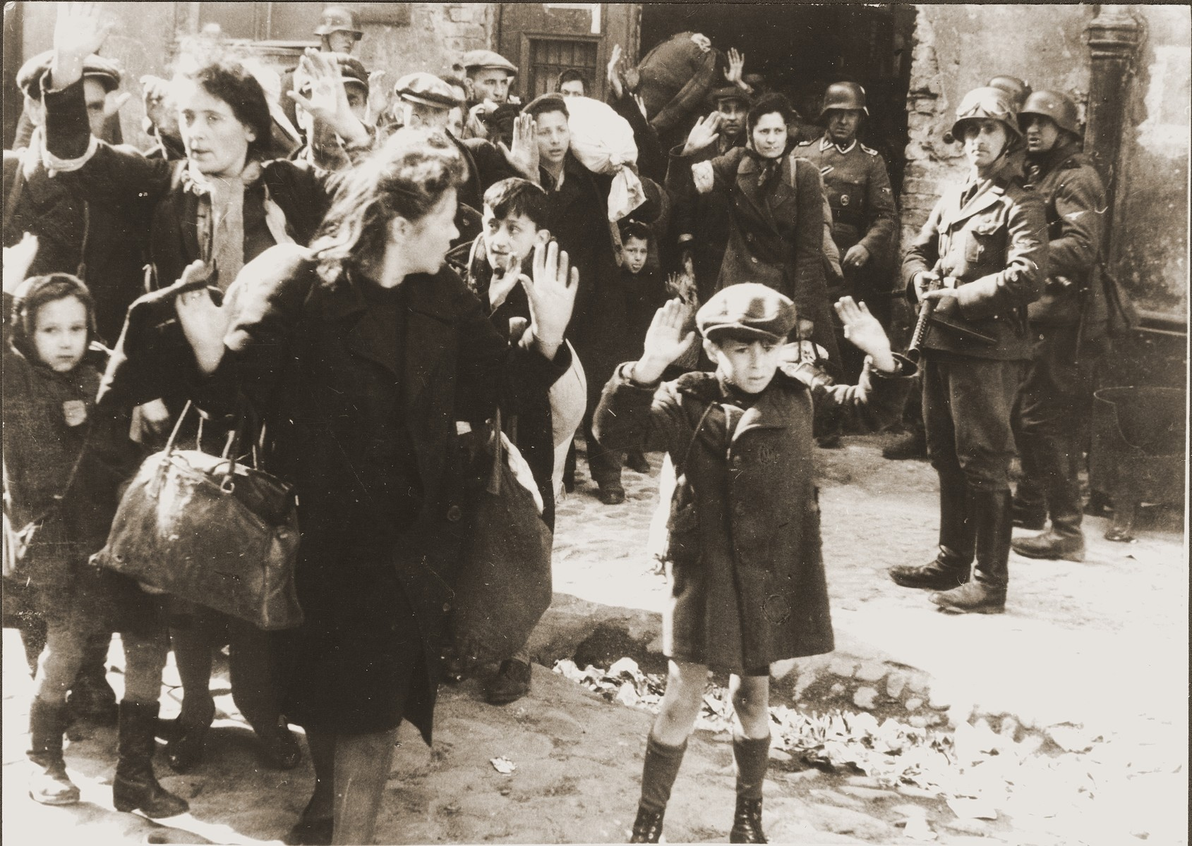 "Jews captured by SS and SD troops during the suppression of the Warsaw ghetto uprising are forced to leave their shelter and march to the Umschlagplatz for deportation.    The original German caption reads: ""Pulled from the bunkers by force.""  The SD trooper pictured second from the right, is SS-Rottenfuehrer Josef Bloesche, who was identified by Polish authorities using this photograph.  Bloesche was tried for war crimes by a Polish court in 1969, sentenced to death and executed in July of that year.    The little girl on the left has been identified as Hanka Lamet, who is standing next to her mother, Matylda Lamet Goldfinger (the woman second from the left).  The boy carrying the sack has been identified as Leo Kartuzinsky and the woman in the front has been identified as Chana Zeilinwarger.  Numerous people have identified the boy in the foreground as either Arthur Domb Semiontek, Israel Rondel, Tsvi Nussbaum or Levi Zeilinwarger, but none of these identifications can be conclusively corroborated.  Original caption from donated photograph reads:  ""The following pictures are copies of the book conaning the report of the German commander who was responsible for cleaning out that ghetto in Warsaw, Poland.  This report, in the form of a leather bound book, was presented as evidence by the U.S. prosecution, Maj. Frank Walsh, at the international tribunal trials at Nurnberg, Germany."""