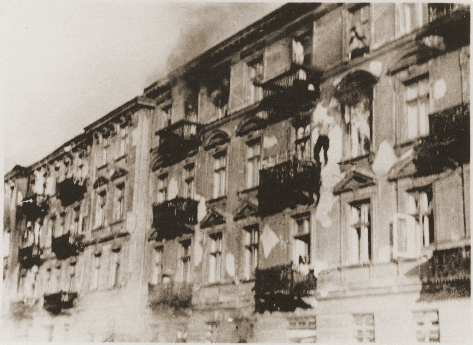 "A Jewish man leaps to his death from the top storey window of an apartment block during the suppression of the Warsaw ghetto uprising.  This photo was taken on the fourth day of the ghetto clearing operation.  The original German caption reads: ""Bandits jump to escape capture."""