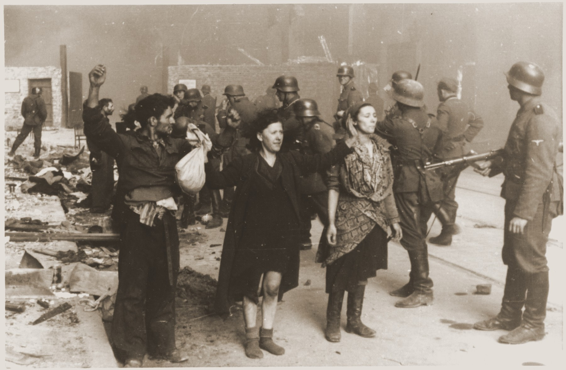 "SS troops guard members of the Jewish resistance captured during the suppression of the Warsaw ghetto uprising.  The original German caption reads: ""These bandits offered armed resistance."""