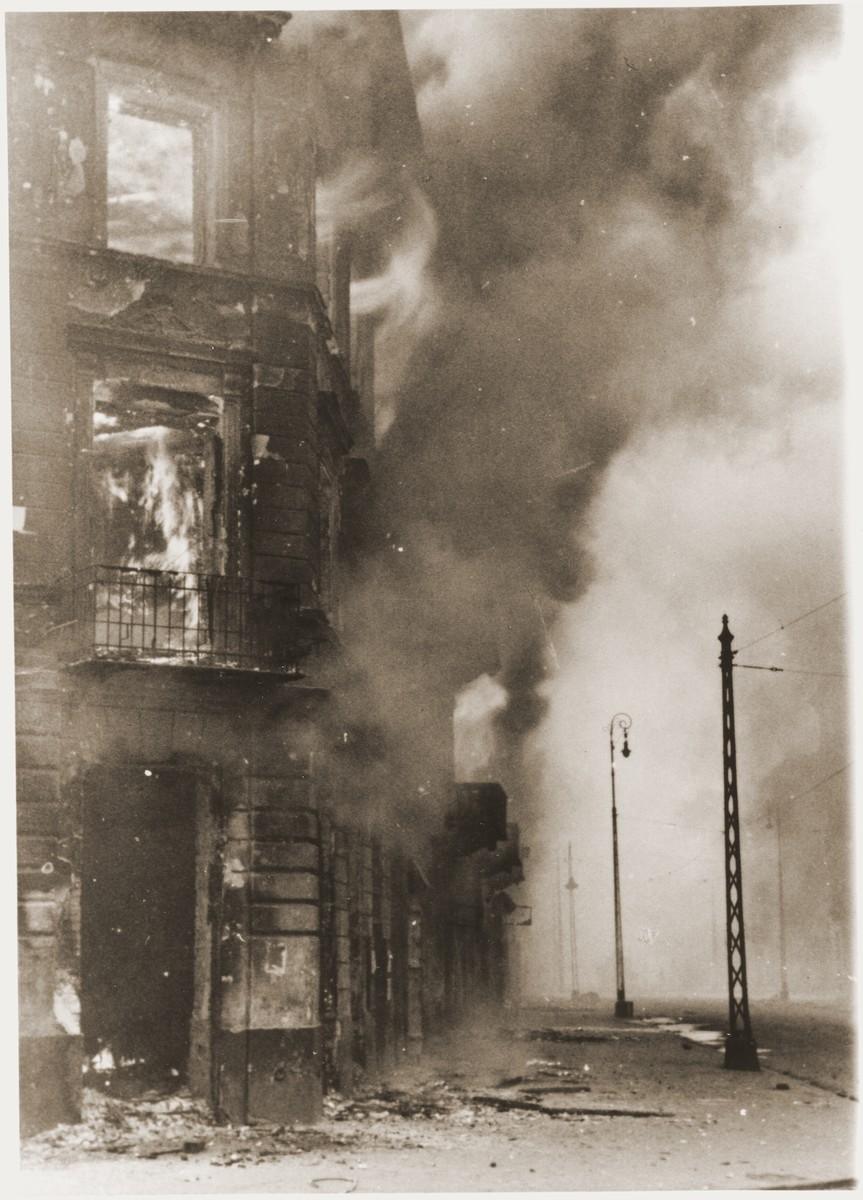 """Apartment buildings razed by the SS burn during the suppression of the Warsaw ghetto uprising.    The original caption (translated from German) reads, """"A housing block being destroyed."""""""