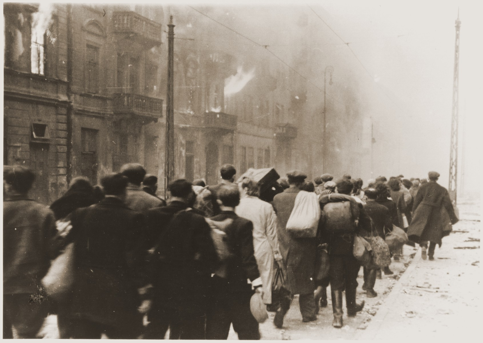 "Jews captured during the Warsaw ghetto uprising are marched to the Umschlagplatz for deportation.    The original German caption reads: ""To the Umschlagplatz."""