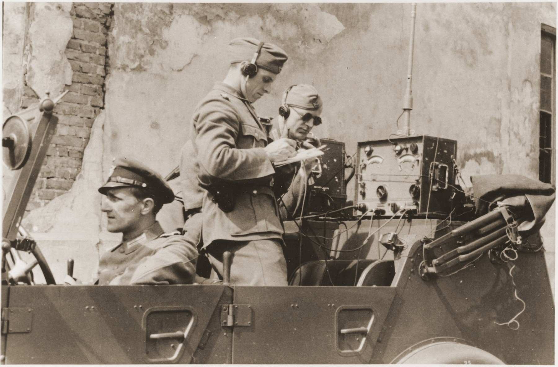 "German policemen operate the radio command car during the suppression of the Warsaw ghetto uprising.  The original German caption reads: ""In the radio car of the command post."""