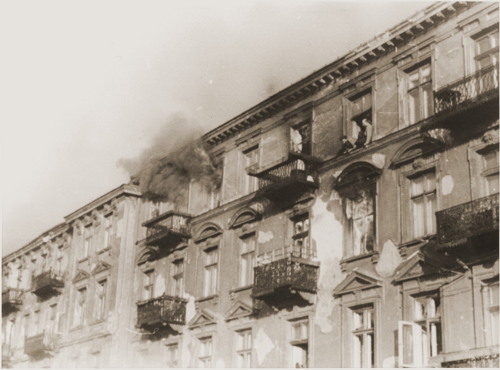 "A man perched on the ledge outside of a fourth story window prepares to commit suicide by jumping rather than be captured by the SS on the fourth day of the suppression of the Warsaw ghetto uprising.  The original German caption reads: ""Bandits jump to escape arrest."""