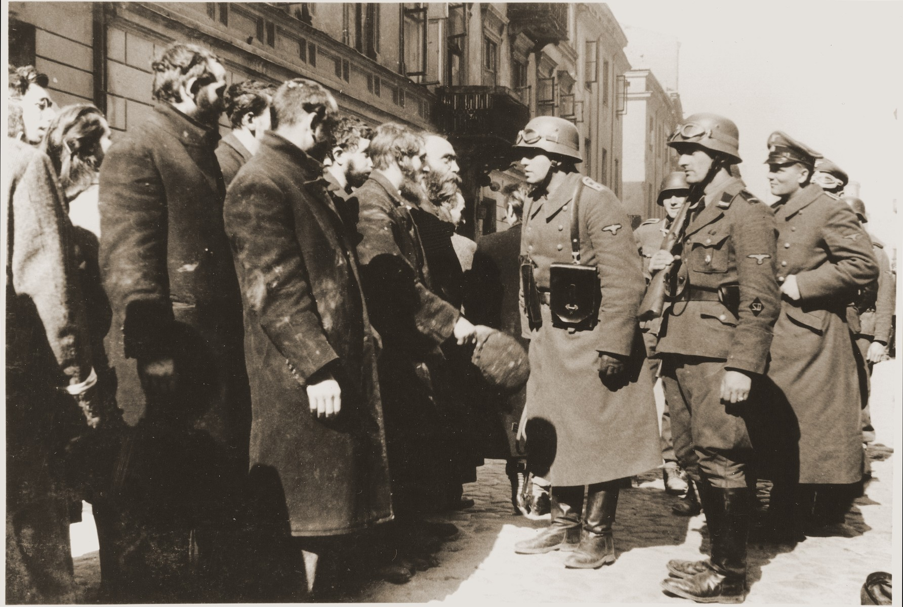 "An SS Sergeant (Oberscharfuehrer) interrogates religious Jews captured during the suppression of the Warsaw ghetto uprising.  The original German caption reads: ""Jewish rabbis.""  Among those pictured is Rabbi Heschel Rappaport.  Original caption from donated photograph reads:  ""The following pictures are copies of the book conaning the report of the German commander who was responsible for cleaning out that ghetto in Warsaw, Poland.  This report, in the form of a leather bound book, was presented as evidence by the U.S. prosecution, Maj. Frank Walsh, at the international tribunal trials at Nurnberg, Germany."""