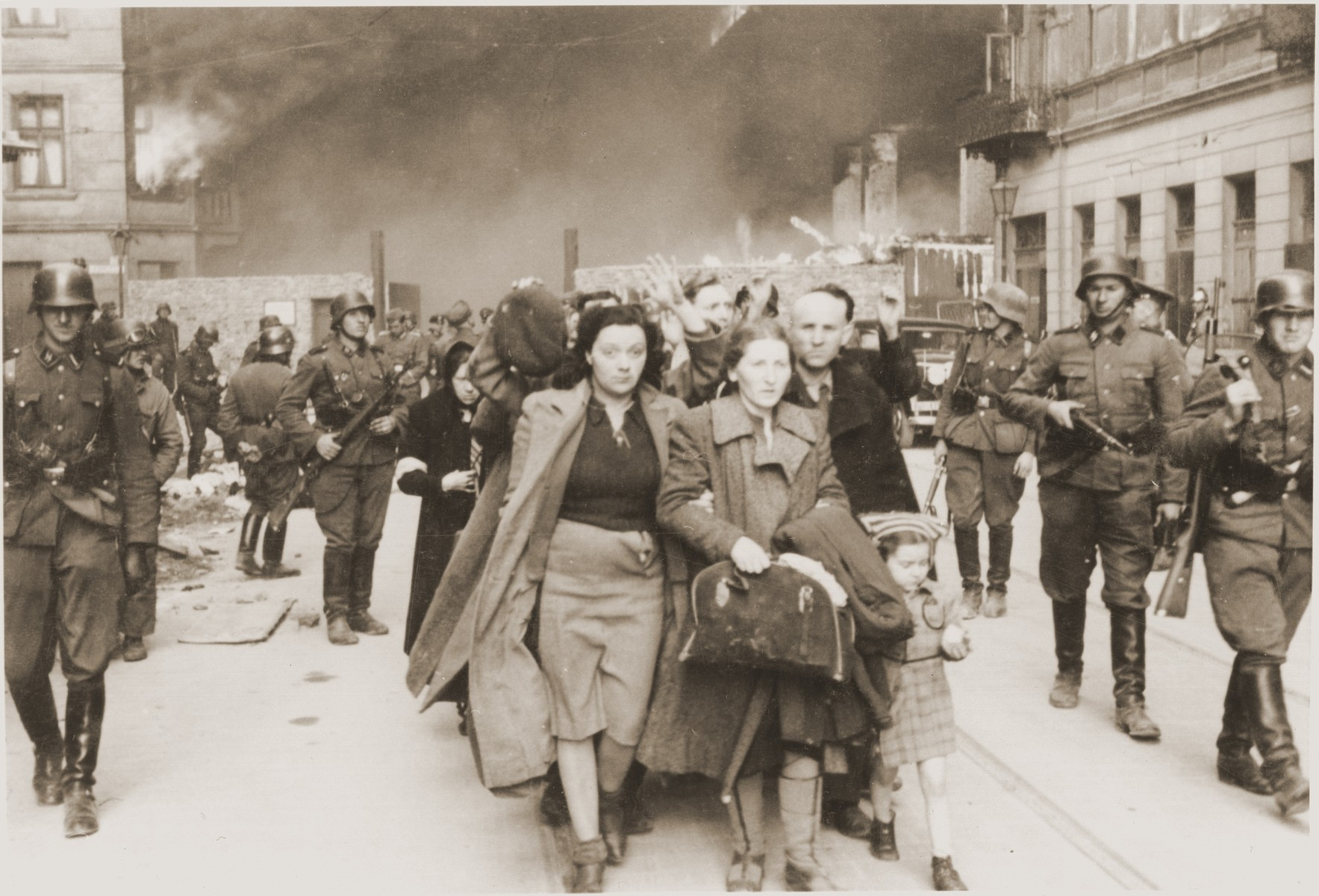 "Jews captured during the suppression of the Warsaw ghetto uprising are marched to the Umschlagplatz for deportation.    The original German caption reads: ""To the Umschlagplatz.""    The woman at the head of the column, on the left, is Yehudit Neyer (born Tolub).  She is holding onto the right arm of her mother-in-law.  The child is the daughter of Yehudit and her father, Avraham Neyer, a member of the Bund, who can be seen just behind the little girl.  Of the four, only Avraham survived the war.  He currently lives in Israel.   The original caption from donated photograph reads,  ""The following pictures are copies of the book containing the report of the German commander who was responsible for cleaning out the ghetto in Warsaw, Poland.  This report, in the form of a leather bound book, was presented as evidence by the U.S. prosecutino, Maj. Frank Walsh, at the International tribunal trials at Nurnnberg, Germany."""