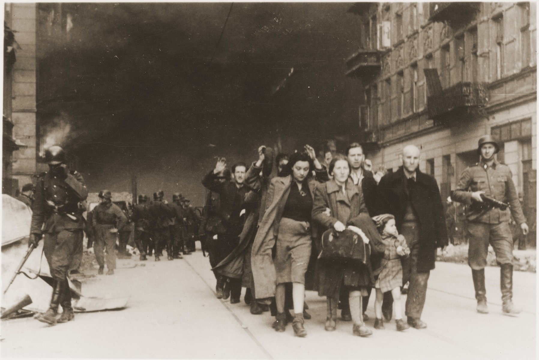 "Jews captured during the suppression of the Warsaw ghetto uprising are led away from the burning ghetto by SS guards.    The original German caption reads: ""Pulled from the bunkers by force.""    The woman at the head of the column, on the left, is Yehudit Neyer (born Tolub).  She is holding onto the right arm of her mother-in-law.  The child is the daughter of Yehudit and her father, Avraham Neyer, who can be seen to the little girl's left.  Avraham was a member of the Bund.  Of the four, only Avraham survived the war.  He currently lives in Israel."