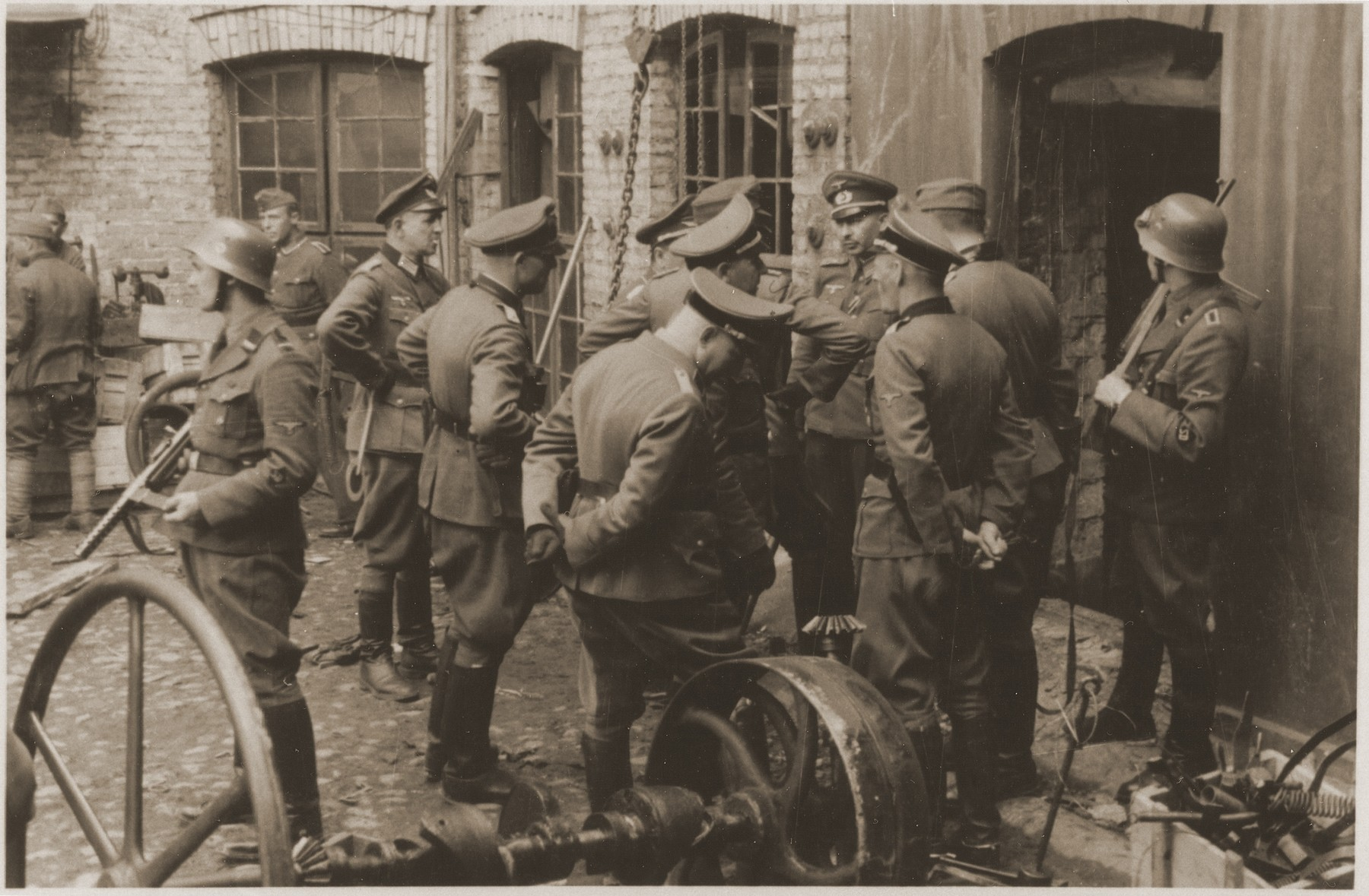 "SS and German army officers, accompanied by SD guards, discuss the evacuation of a factory in the Warsaw ghetto during the uprising.    The original caption reads: ""Discussing the evacuation of an enterprise."""