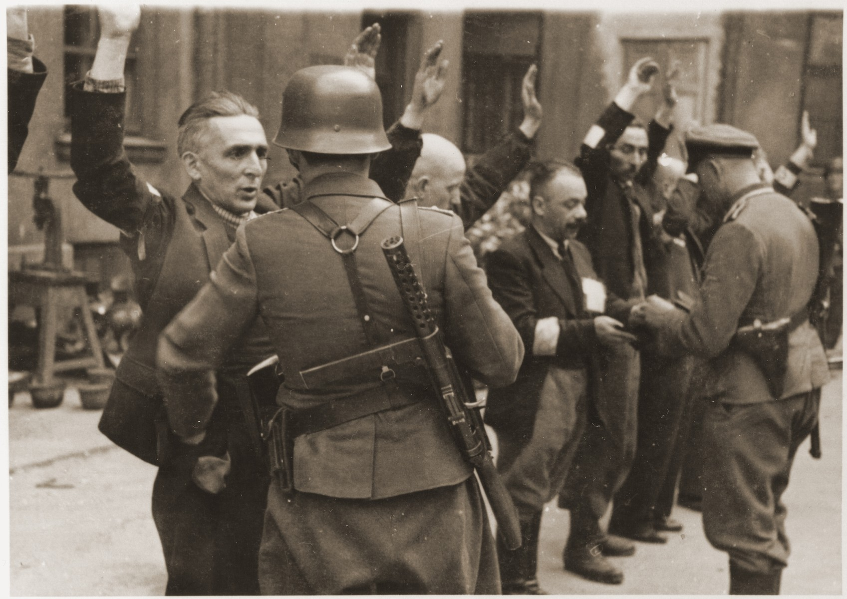 "SS troops and officers search the Jewish department heads of the Brauer armaments factory during the suppression of the Warsaw ghetto uprising.    The original German caption reads: ""The Brauer firm.""  Original caption from donated photograph reads:  ""The following pictures are copies of the book conaning the report of the German commander who was responsible for cleaning out that ghetto in Warsaw, Poland.  This report, in the form of a leather bound book, was presented as evidence by the U.S. prosecution, Maj. Frank Walsh, at the international tribunal trials at Nurnberg, Germany."""
