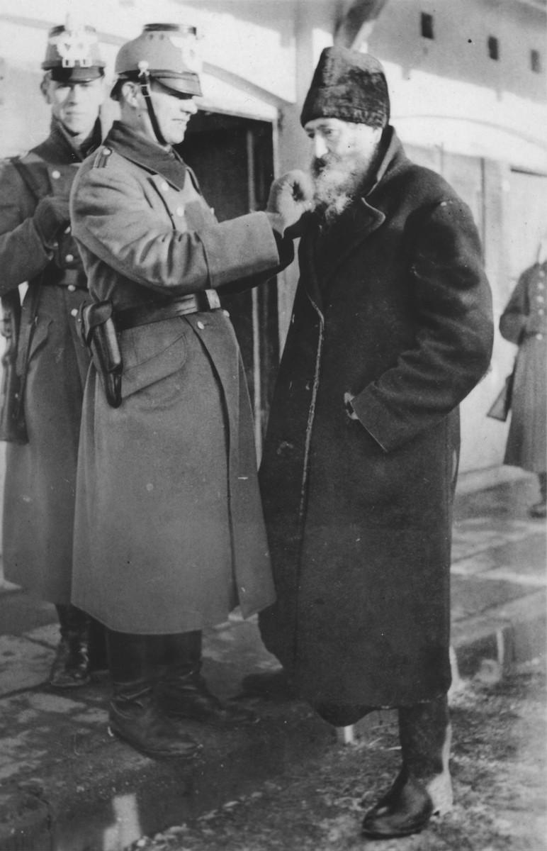 A German policeman cuts off the beard of a Jew in Zawiercie.