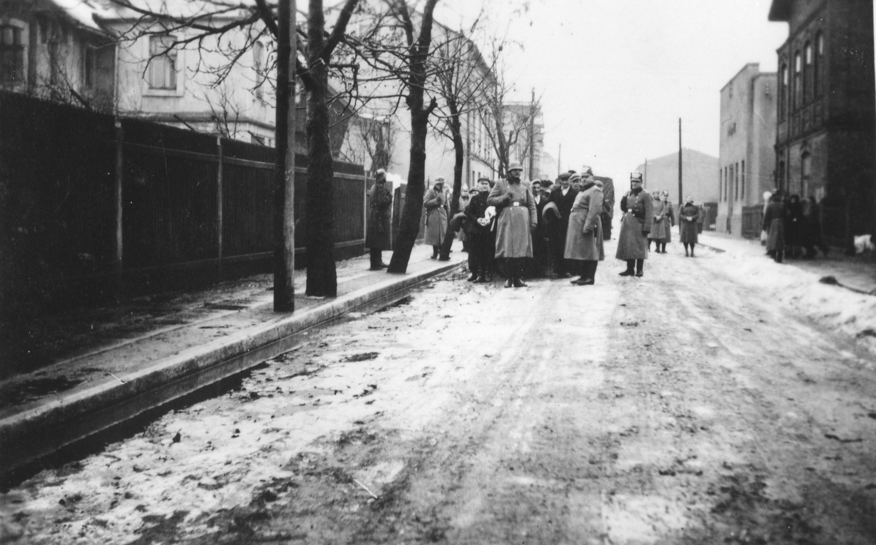 Jews are rounded up and assembled in columns on a street in the Zawiercie ghetto.