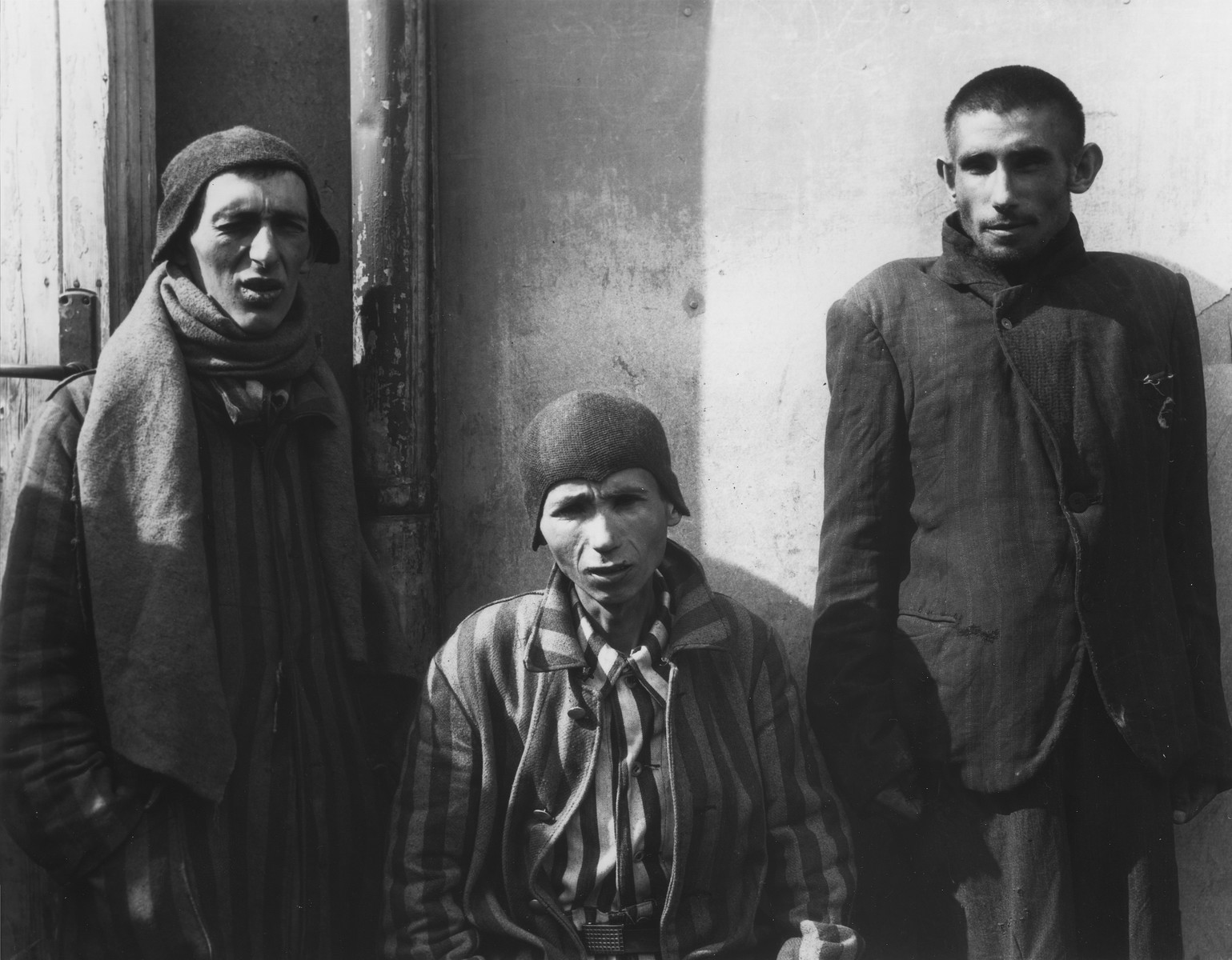 "Three survivors pose outside a barracks in the Dachau concentration camp immediately after the liberation.  The original Signal Corps caption reads, ""DACHAU CONCENTRATION CAMP.  Horrors worse than those found in the German concentration camps of Buchenwald and Belsen were discovered in the stinking hell-hole of Dachau, captured by troops of the 42nd and 45th Infantry Divivions of the Seventh U.S. Army April 30, 1945.  More than 32,000 prisoners were liberated, among those some Englishmen, Canadians and Americans.  The camp was formally surrendered by an SS lieutenant carrying a white flag, accompanied by a Swiss Red Cross official, but SS troops opened fire as American troops approached the main entrance.  The Germans were shot down.  Three prisoners were electrocuted when they tried to burst through the electrified wire barrier to welcome the Americans.  SS guards opened fire on other prisoners who went wild with joy and rushed to meet the liberating troops.  Prisoners with access to records said 9,000 people died of hunger, disease or shooting within the past three months at Dachau.  Four thousand more perished during cold Winter months.  When Americans entered the camp, they found 50 open railway cars standing on a siding, apparently full of oiled, dirty clothing but actually found to contain hundreds of corpses piled on top of each other.  They also found a row of kennels where fierce doges were kept to set after escaping men.  They discovered gas extermination chambers, incinerators full of naked bodies, bodies marked for dissection and the bodies of several small children.   BIPPA                                                        EA 64858  THIS PHOTO SHOWS:  Gaunt, starved and half-dead, these three prisoners, two in striped prison garb, are evidence of the horrors of Dachau.  U.S. Signal Corps Photo ETO-HQ-45-35581. SERVICED BY LONDON OWI TO LIST B CERTIFIED AS PASSED BY SHAEF CENSOR"""